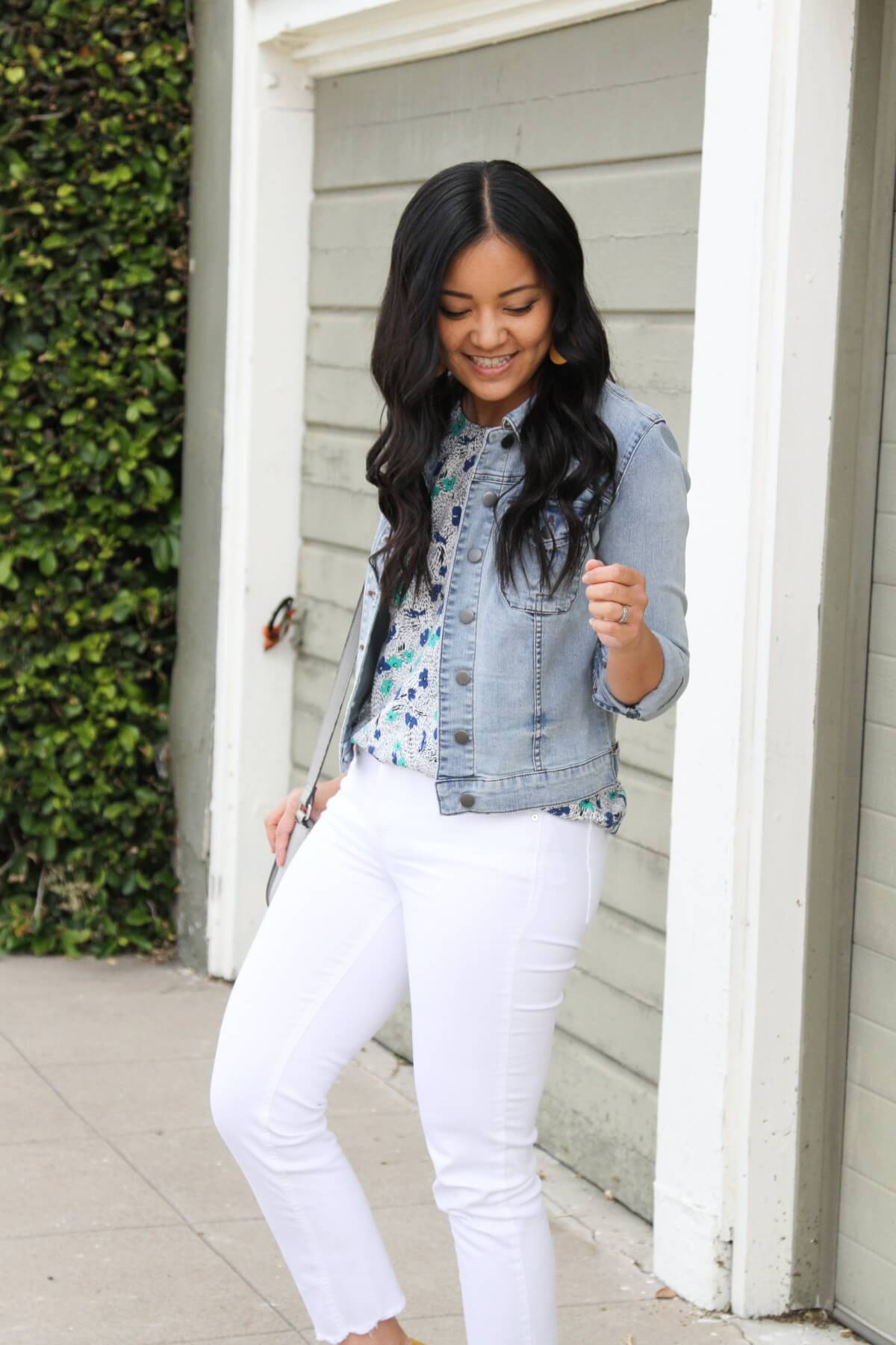Elevated Casual Outfit: blue and green floral top + white jeans + denim jacket + yellow earrings + gray bag
