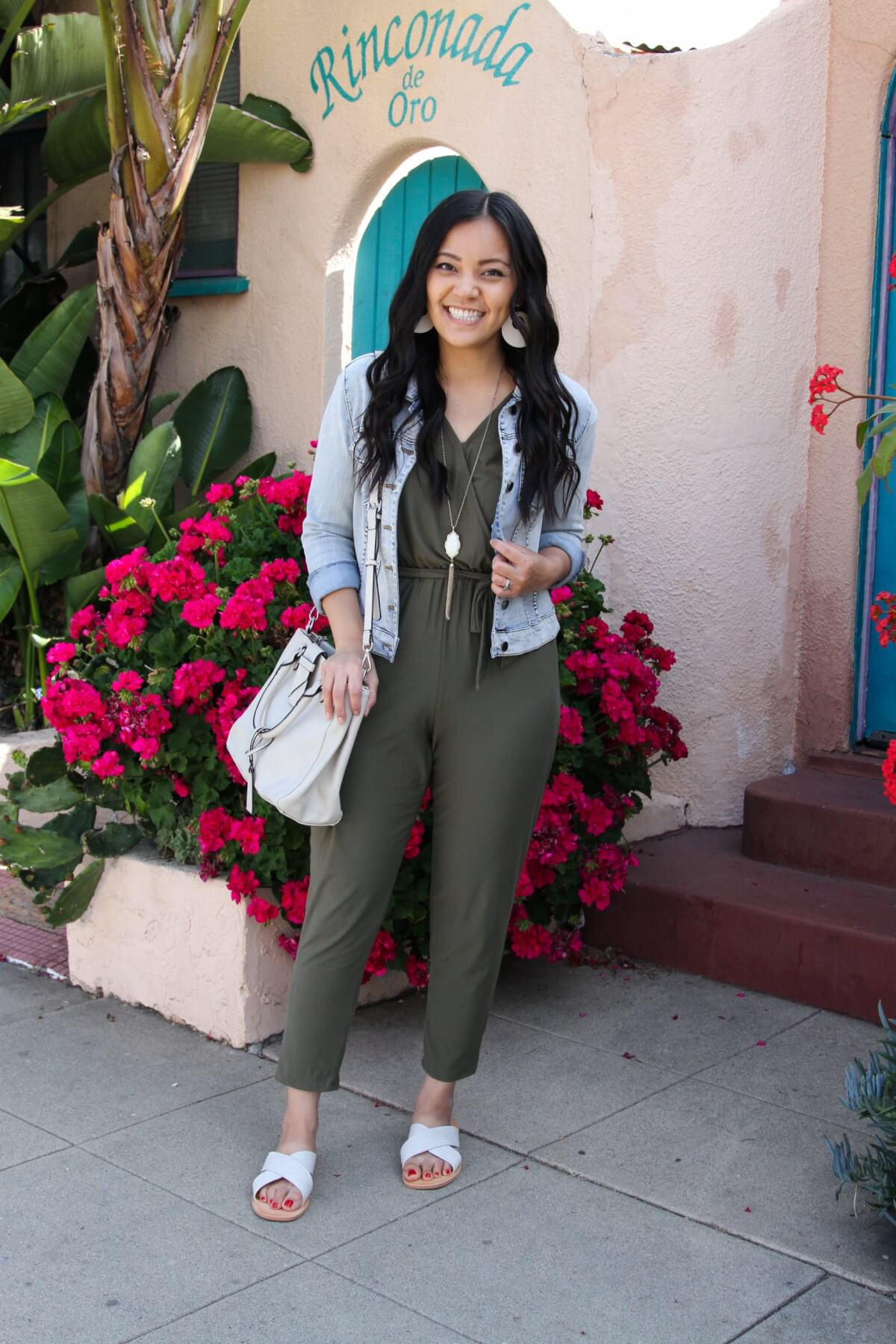 Lunch with Friends Outfit: olive jumpsuit + white slide sandals + denim jacket + white bag + white earrings