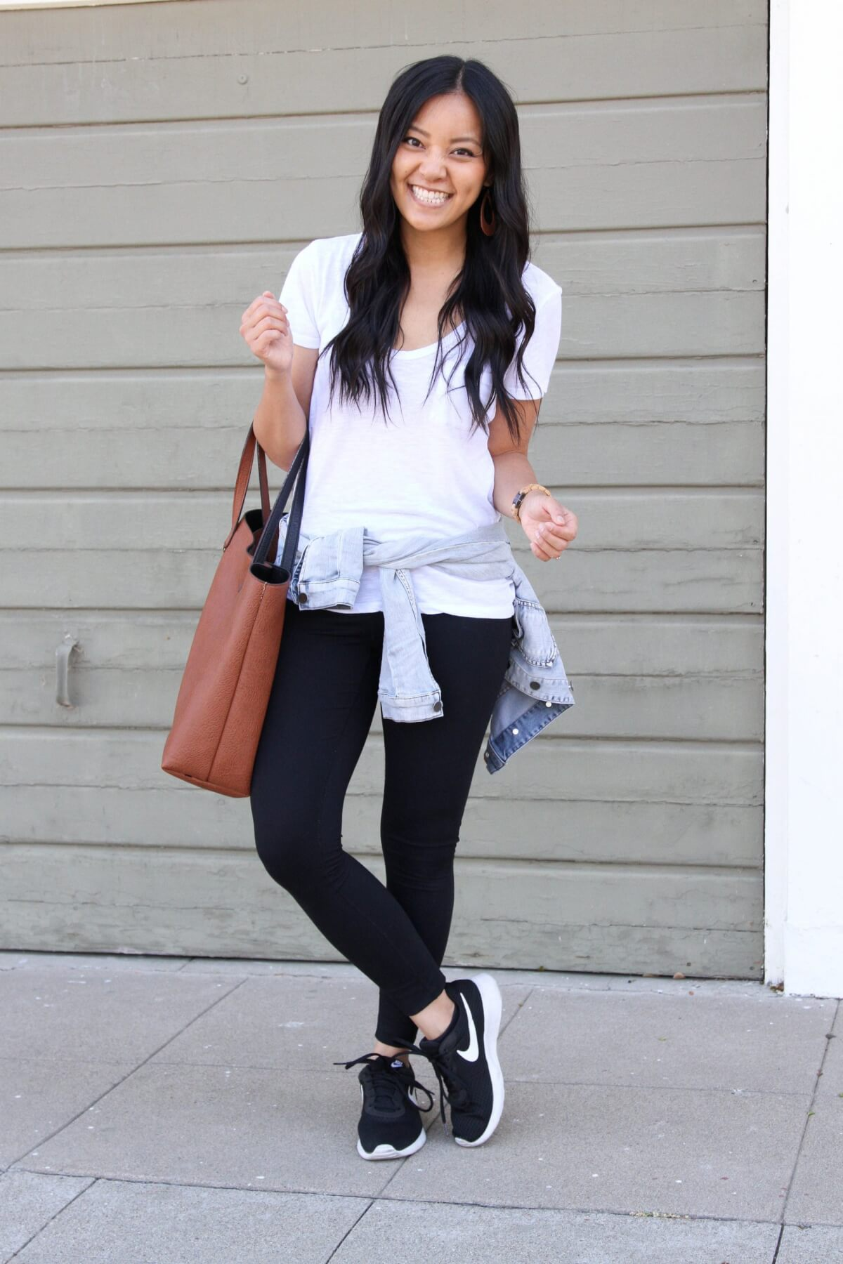 denim jacket outfit: denim jacket + white tee + black leggings + black sneakers + tan earrings + brown tote