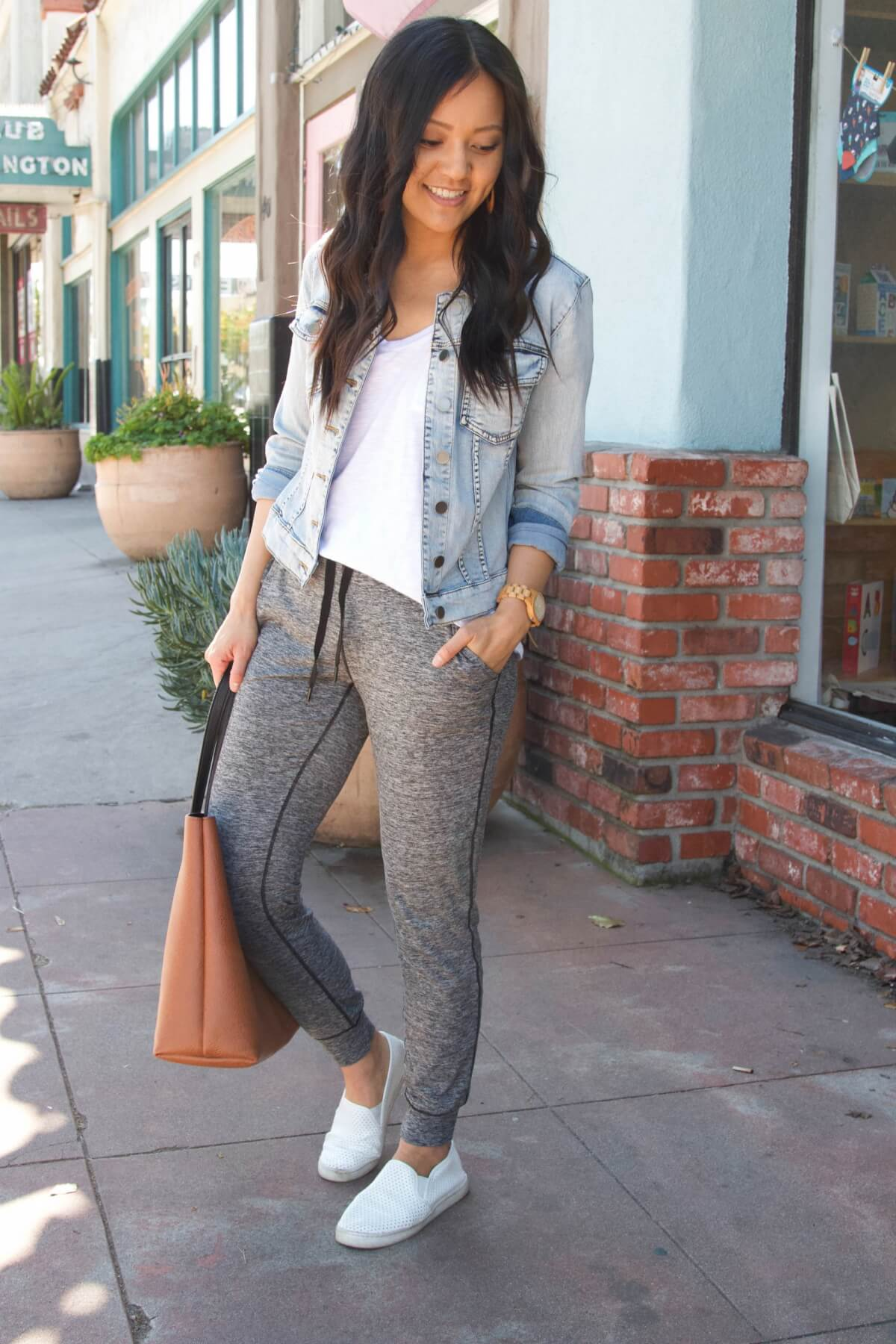 denim jacket outfit: denim jacket + white tee + gray joggers + white sneakers + brown tote