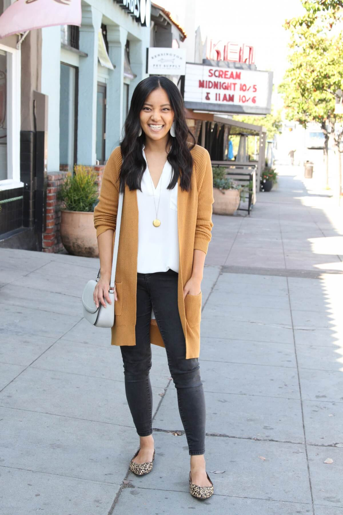 Classic Outfit: white top + camel long cardigan + black jeans + leopard flats + white earrings + pendant necklace + white bag