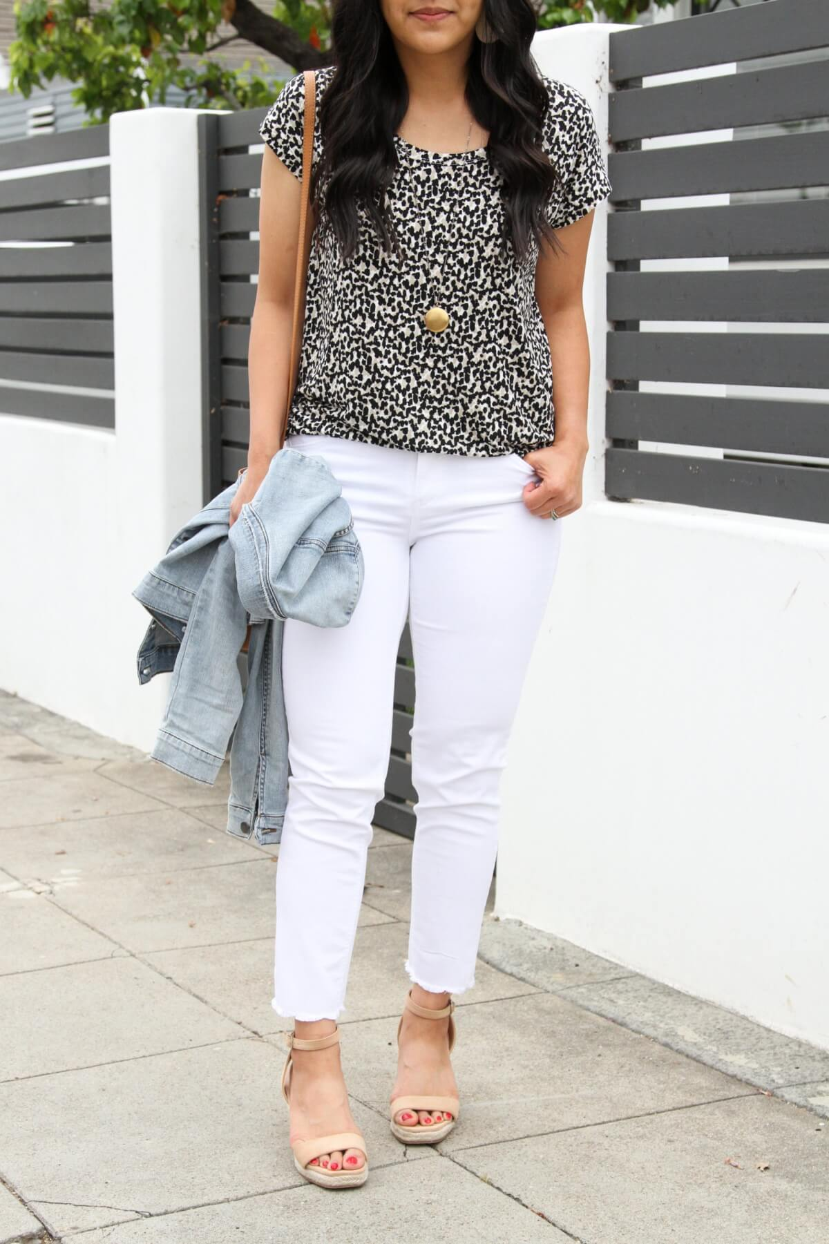 Nicer Casual Outfit: Leopard tee + white jeans + denim jacket + nude wedges + white earrings + pendant necklace + cognac crossbody bag close up