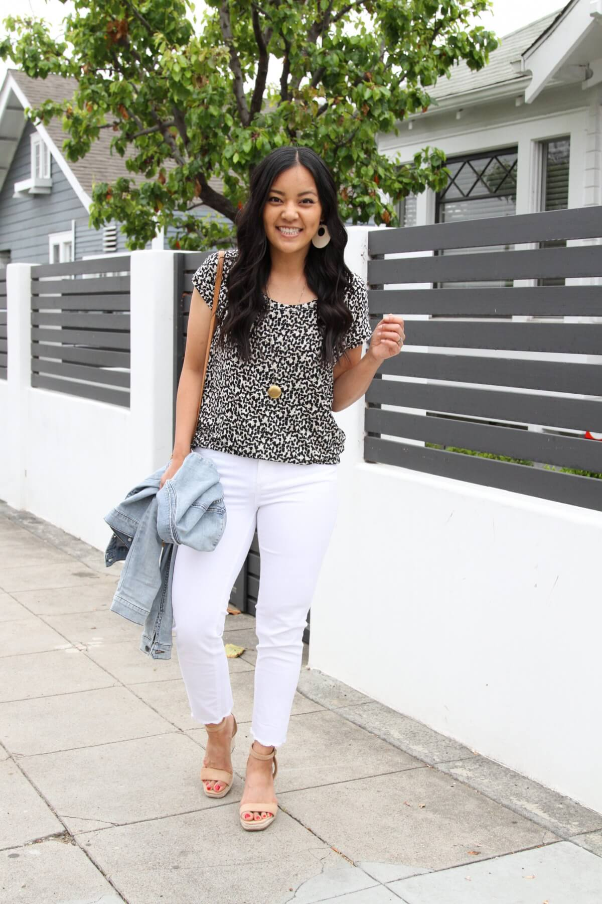 Nicer Casual Outfit: Leopard tee + white jeans + denim jacket + nude wedges + white earrings + pendant necklace + cognac crossbody bag