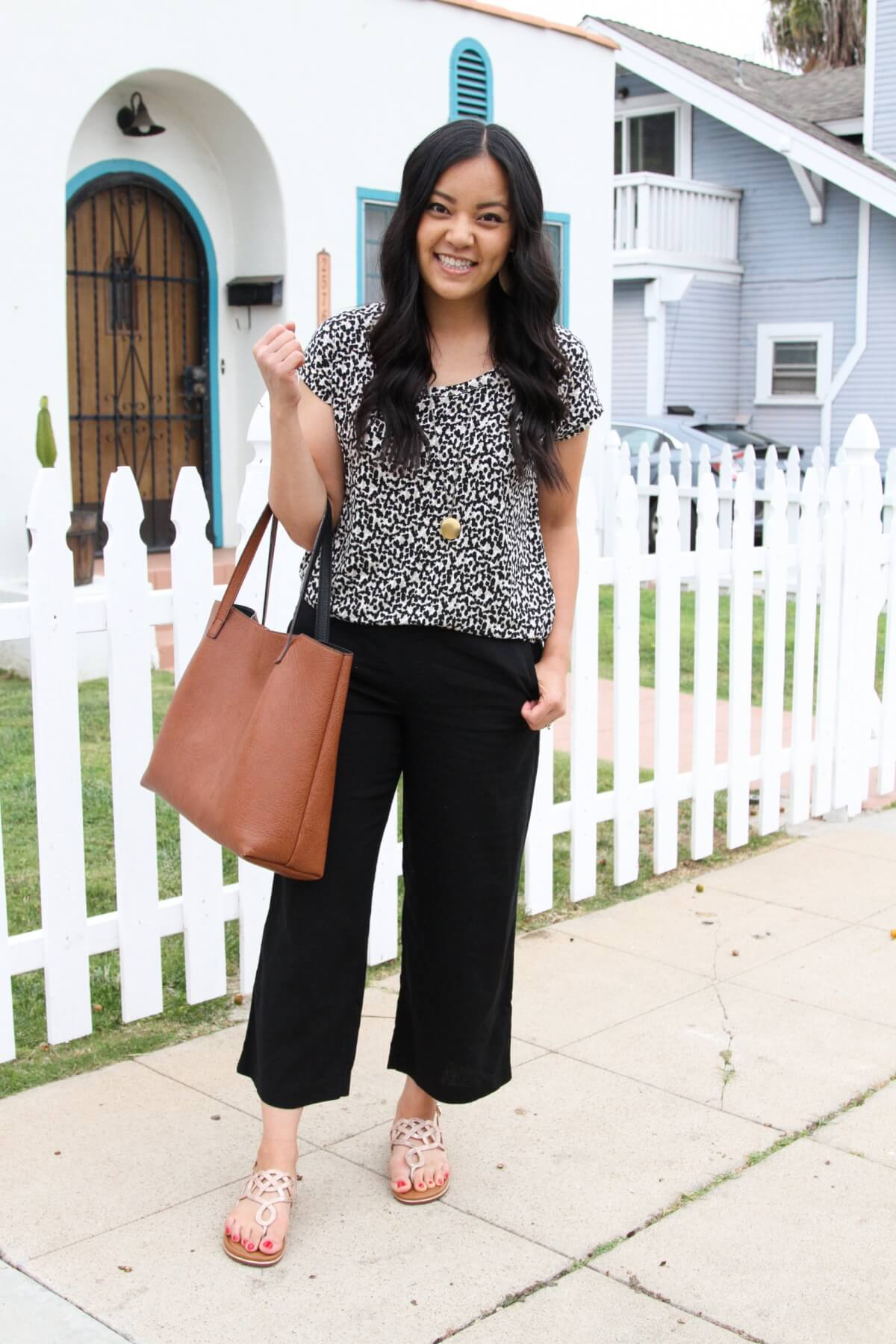 Summer Pants Elevated Outfit: black white beige spotted tee + black wide leg pants + pendant necklace + metallic sandals + tan tote
