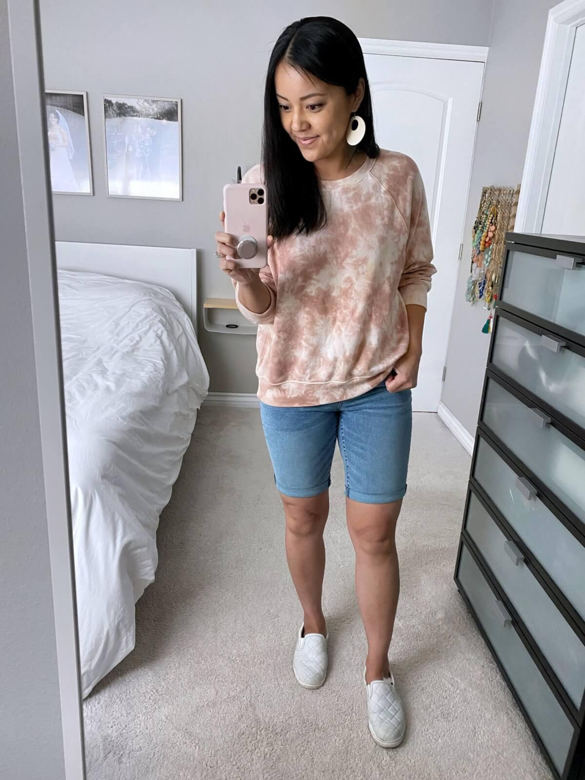 Casual Outfit: Amazon pink tie dye sweatshirt + denim bermuda shorts + white slip-on sneakers + white earrings