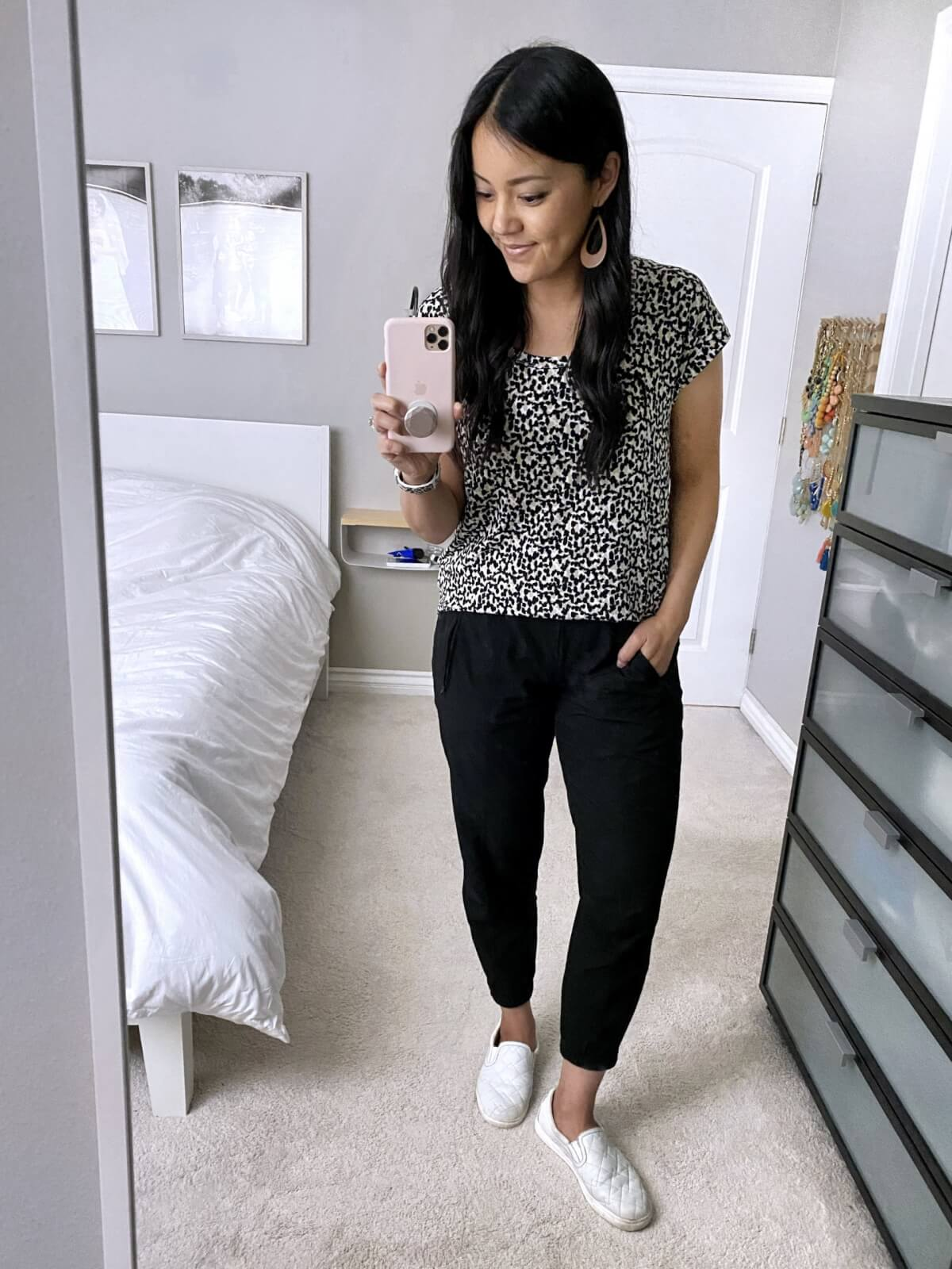 Summer Pants Casual Outfit: black white beige spotted tee + black joggers + tan earrings + white slip-on sneakers