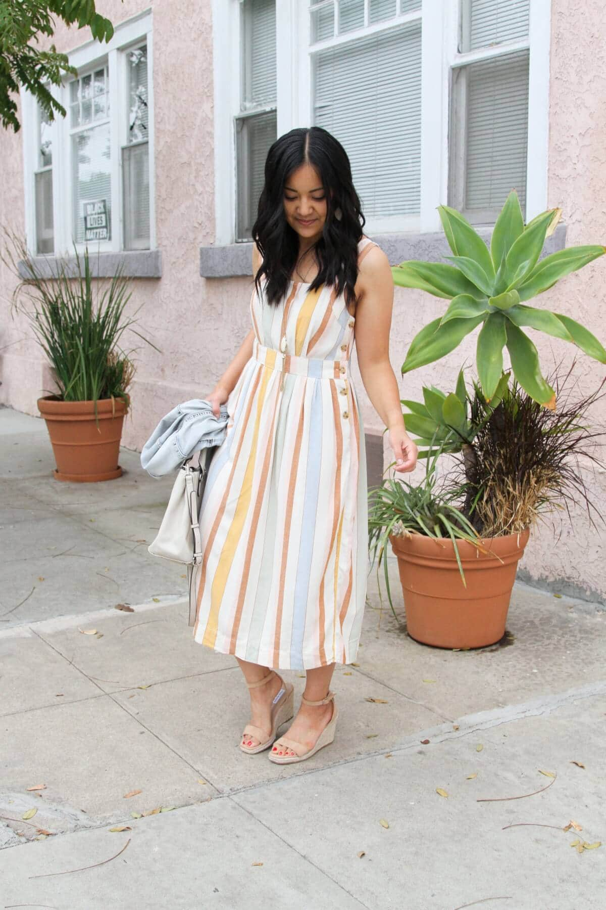 Dressy Outfit: pastel striped midi dress + nude wedges + pendant necklace + white earrings + denim jacket + white bag