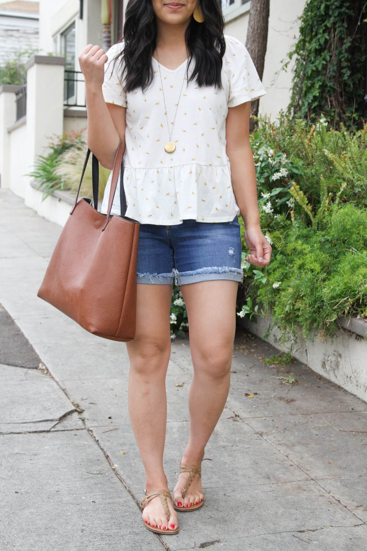 Nicer Casual Outfit: white yellow ditzy peplum top + denim shorts + tan t-strap sandals + yellow earrings + pendant necklace + tan tote close up