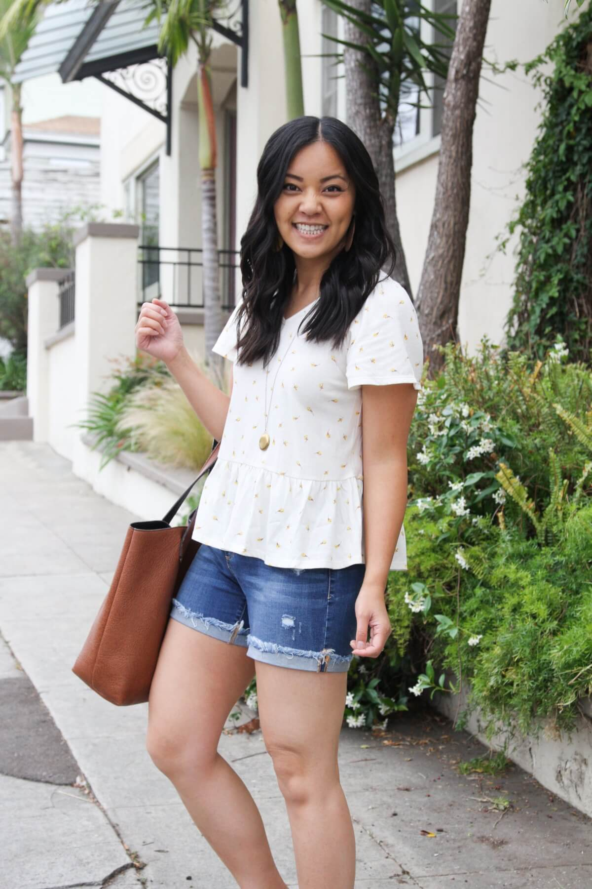 Nicer Casual Outfit: white yellow ditzy peplum top + denim shorts + yellow earrings + pendant necklace + tan tote