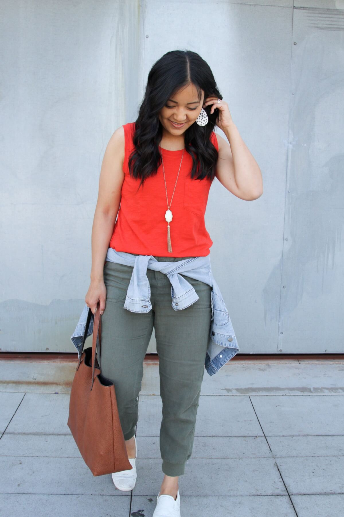 Casual Outfit: orange tank + olive joggers + denim jacket + white slip-on sneakers + white leopard earrings + pendant necklace + tan tote close up