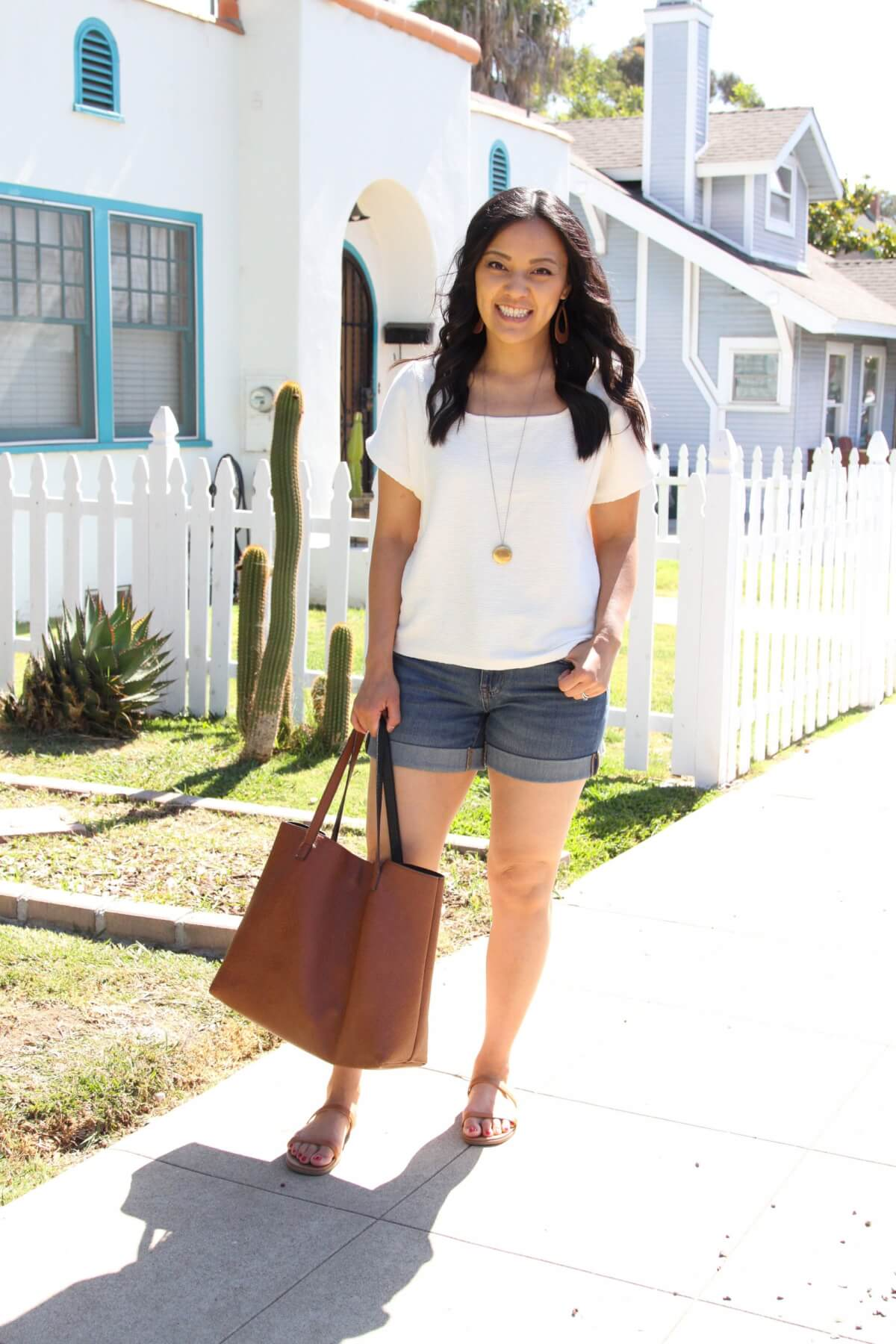 Nicer Casual Summer Outfit: cream square neck top + denim shorts + tan earrings + pendant necklace + tan strappy sandals + tan tote