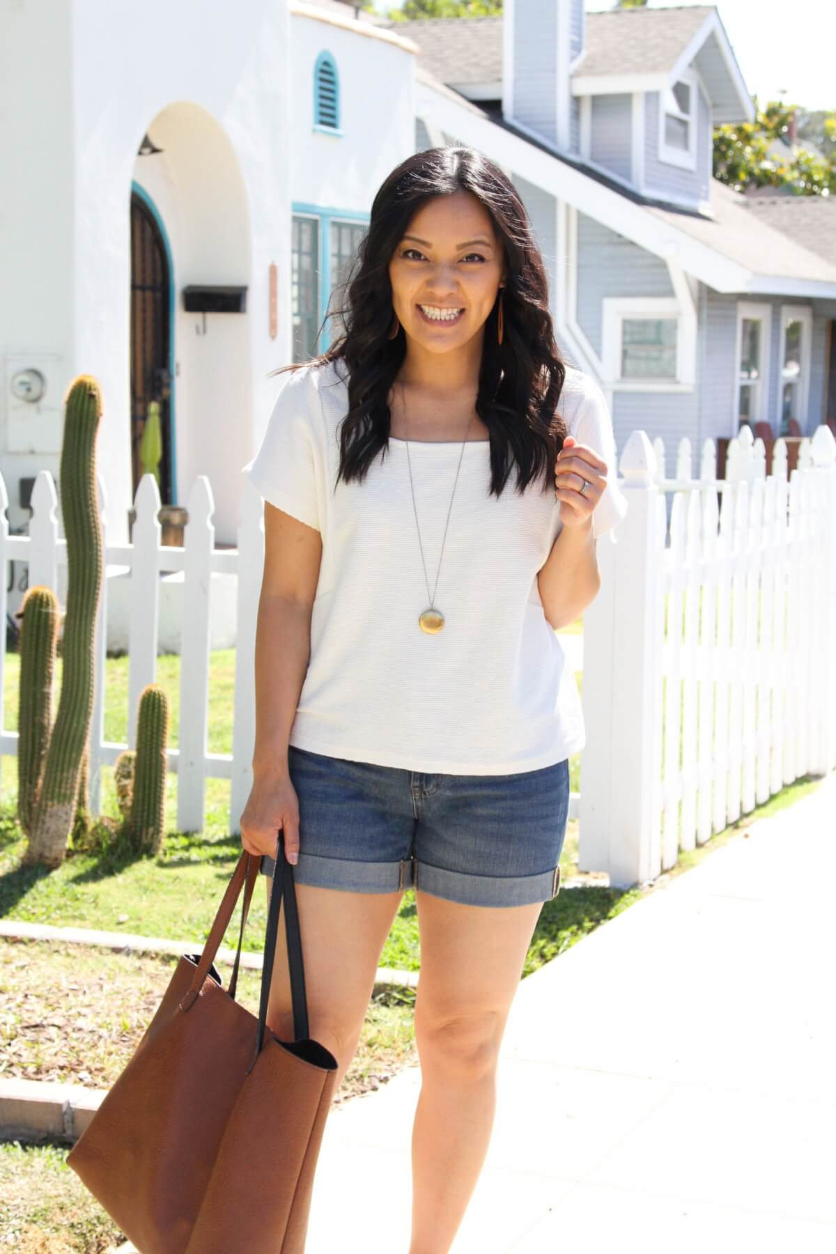 Nicer Casual Summer Outfit: cream square neck top + denim shorts + tan earrings + pendant necklace + tan tote