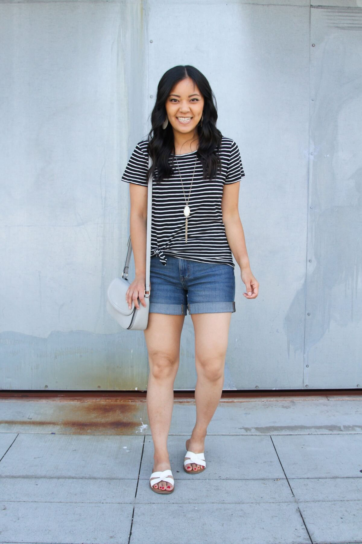 Casual Summer Outfit: black and white striped tee + denim shorts + white slide sandals + pendant necklace + grey crossbody bag