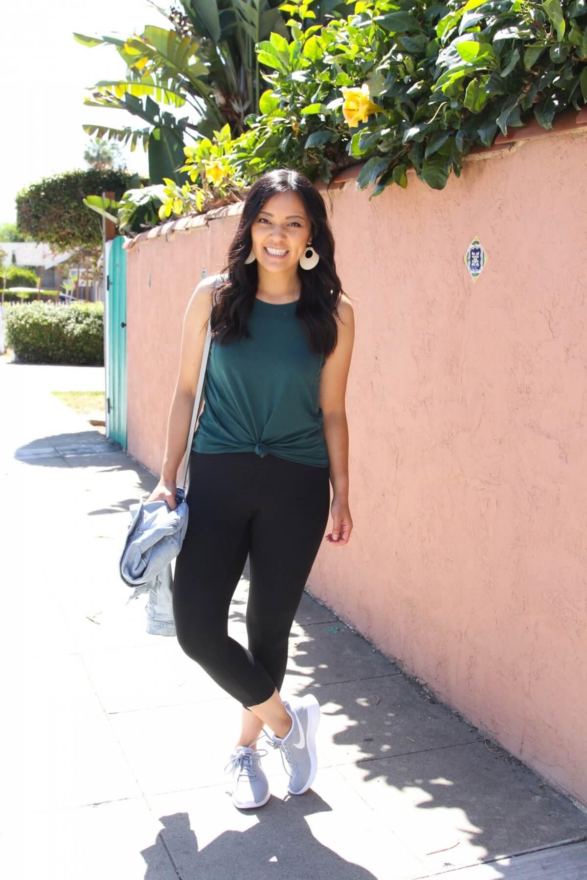 Casual Summer Outfit: forest green tank + black leggings + denim jacket + grey sneakers + white earrings + grey crossbody bag