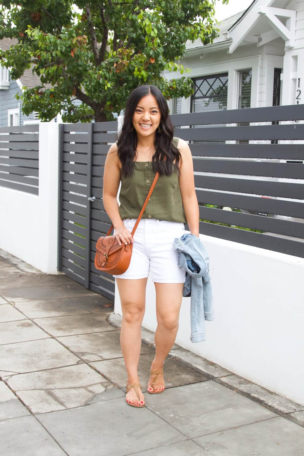 Dressy Casual Summer Outfit: olive button down linen sleeveless top + white shorts + denim jacket + tan t-strap sandals + cognac crossbody bag