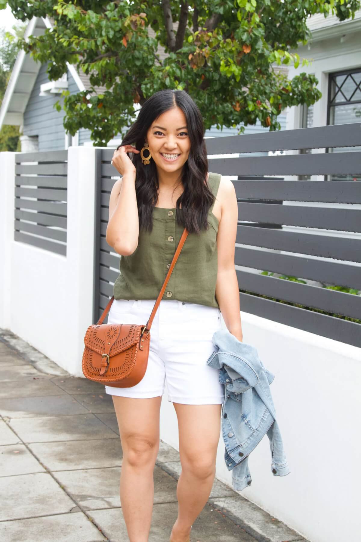 Dressy Casual Summer Outfit: olive button down linen sleeveless top + white shorts + denim jacket + gold dangly earrings + cognac crossbody bag
