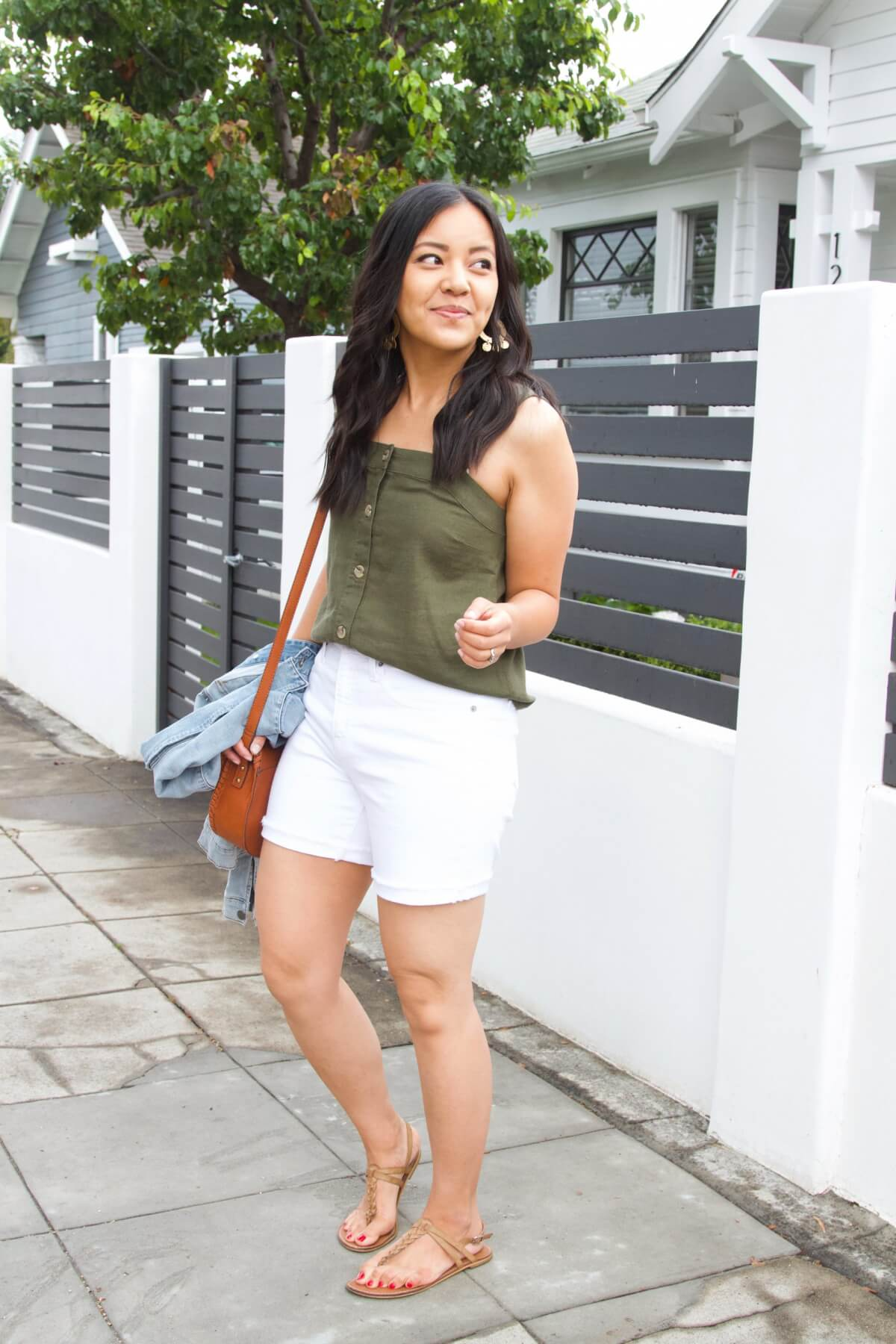 Dressy Casual Summer Outfit: olive button down linen sleeveless top + white shorts + denim jacket + tan t-strap sandals + gold dangly earrings + cognac crossbody bag