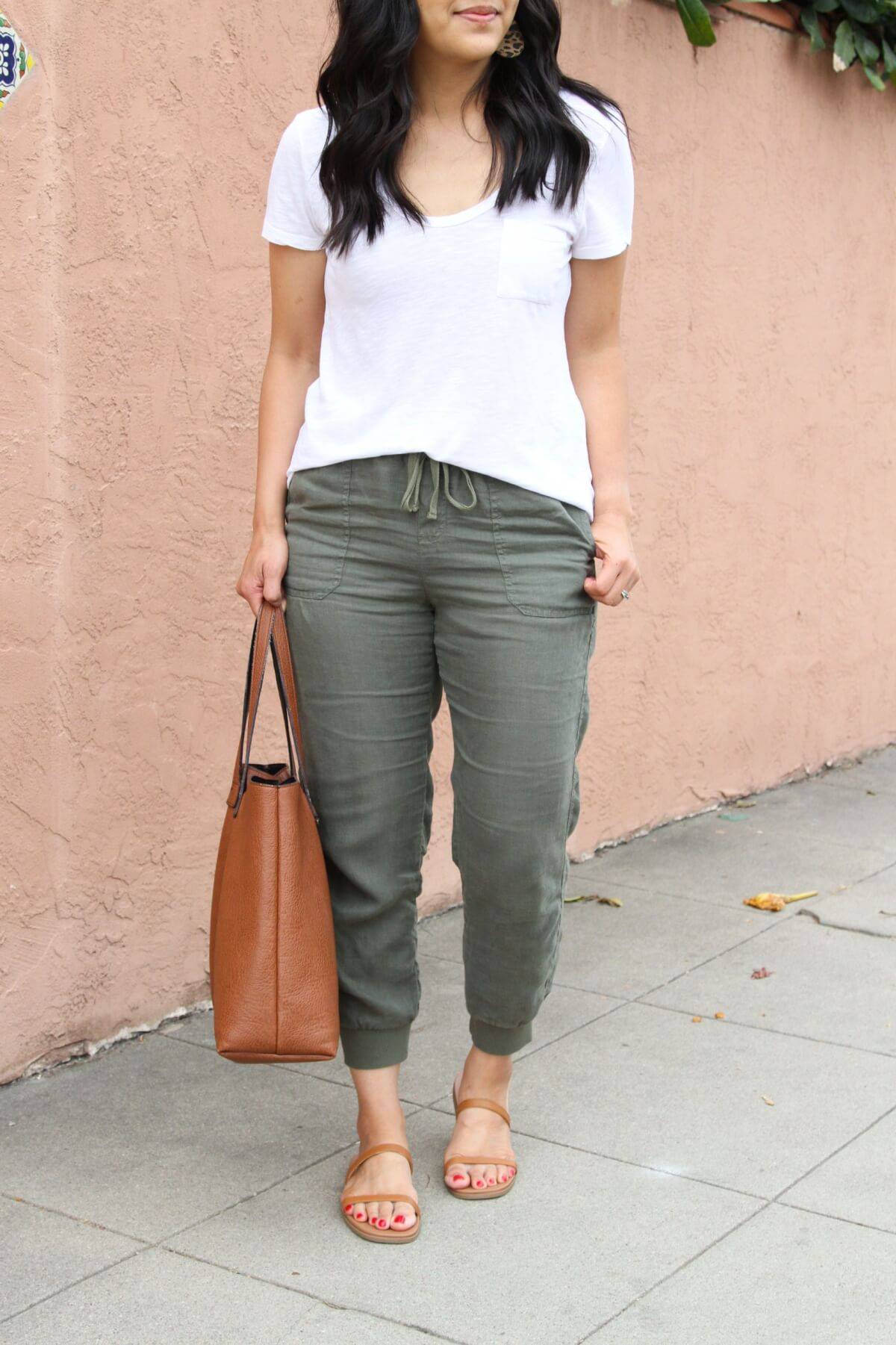 Casual Outfit: olive joggers + white tee + tan leather sandals + leopard earrings + tan tote close-up