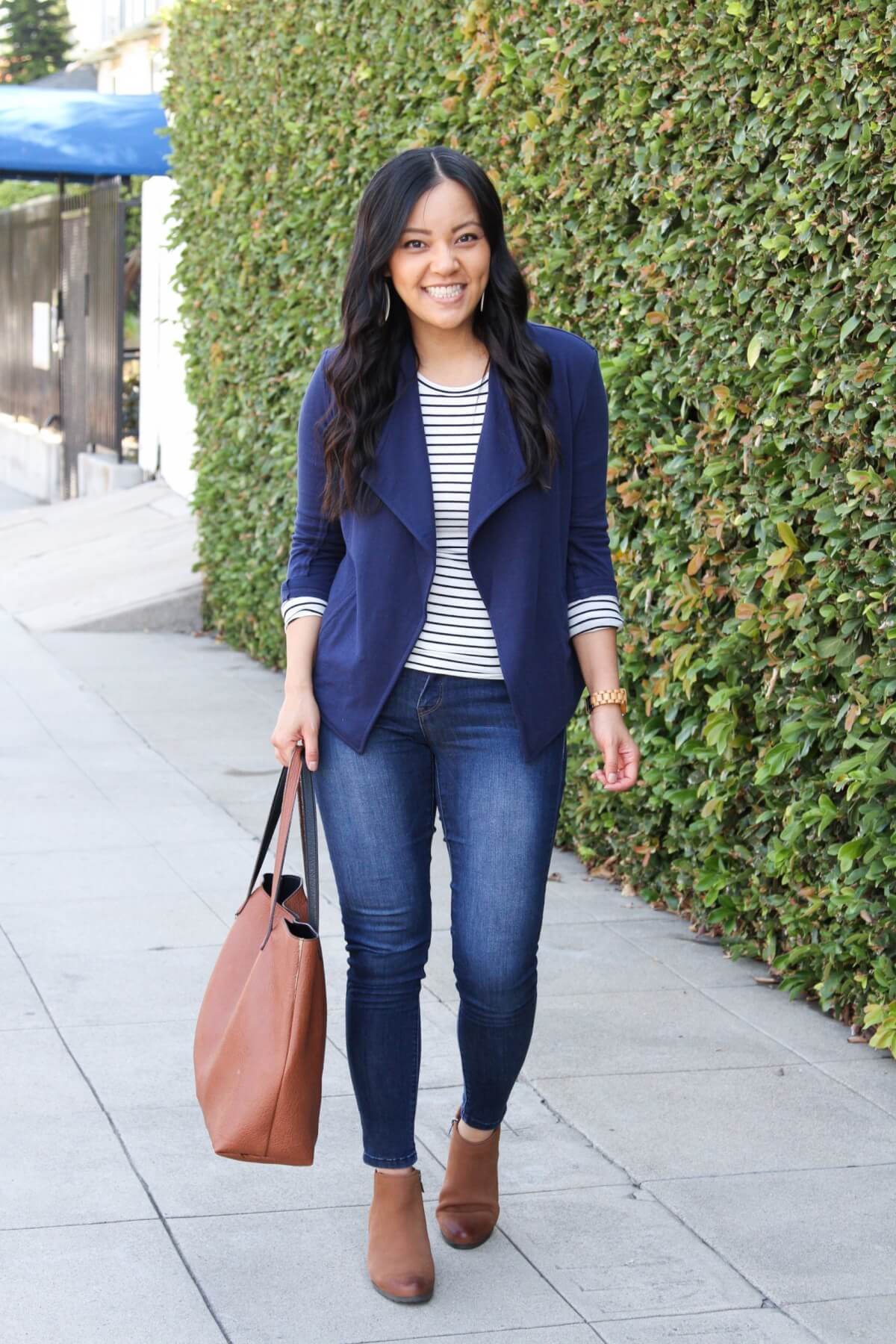 elevated casual outfit: black and white striped long sleeve tee + blue knit blazer + blue skinny jeans + white earrings + tan booties + tan tote