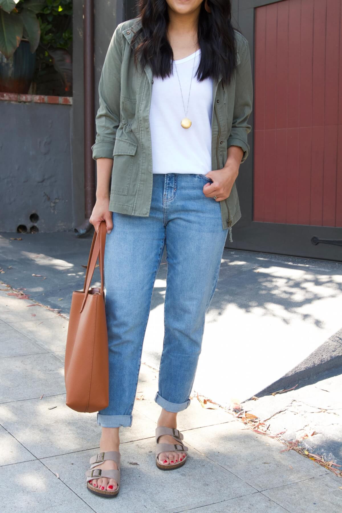 Casual Outfit: white tank + straight leg jeans + utility jacket + pendant necklace + tan tote + birkenstock type sandals close up