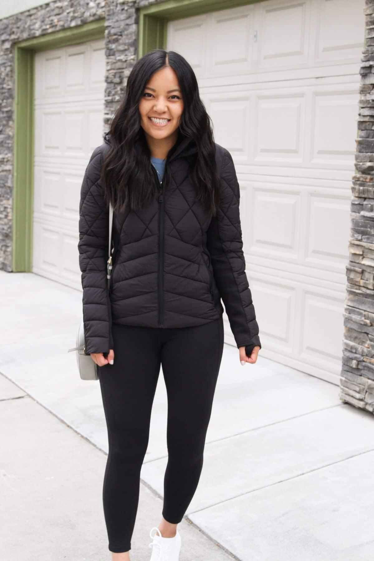 Athleisure Casual Outfit: blue sweatshirt + black leggings + black puffer jacket + white sneakers + gray small crossbody bag