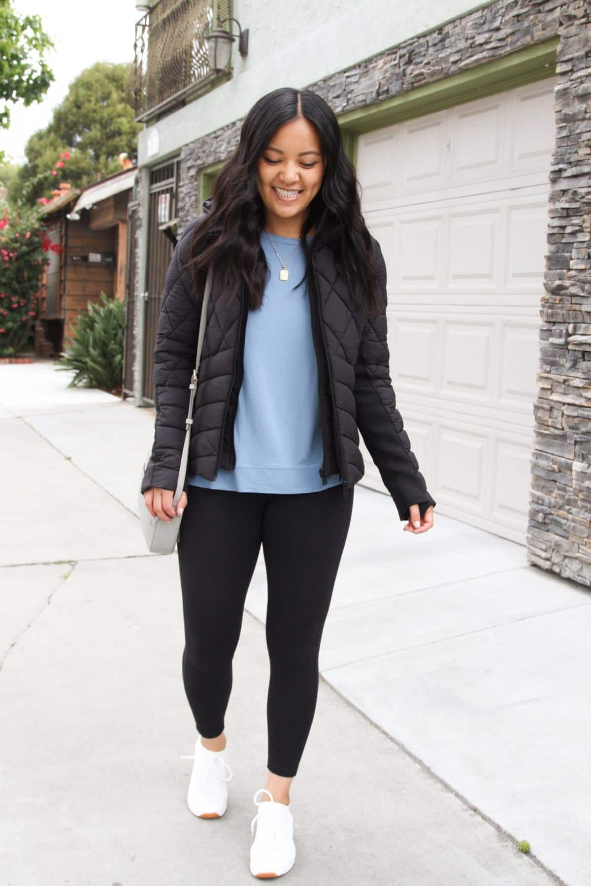Athleisure Casual Outfit: blue sweatshirt + black leggings + black puffer jacket + white sneakers + gold initial pendant necklace + gray small crossbody bag