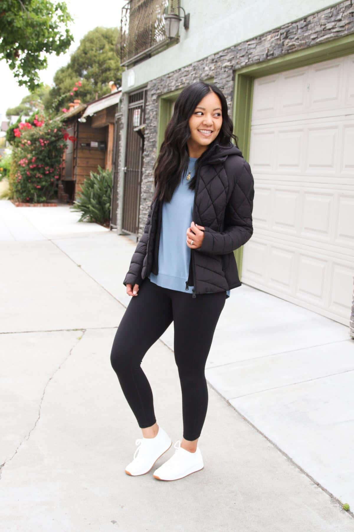 Athleisure Casual Outfit: blue sweatshirt + black leggings + black puffer jacket + white sneakers + gold initial pendant necklace side