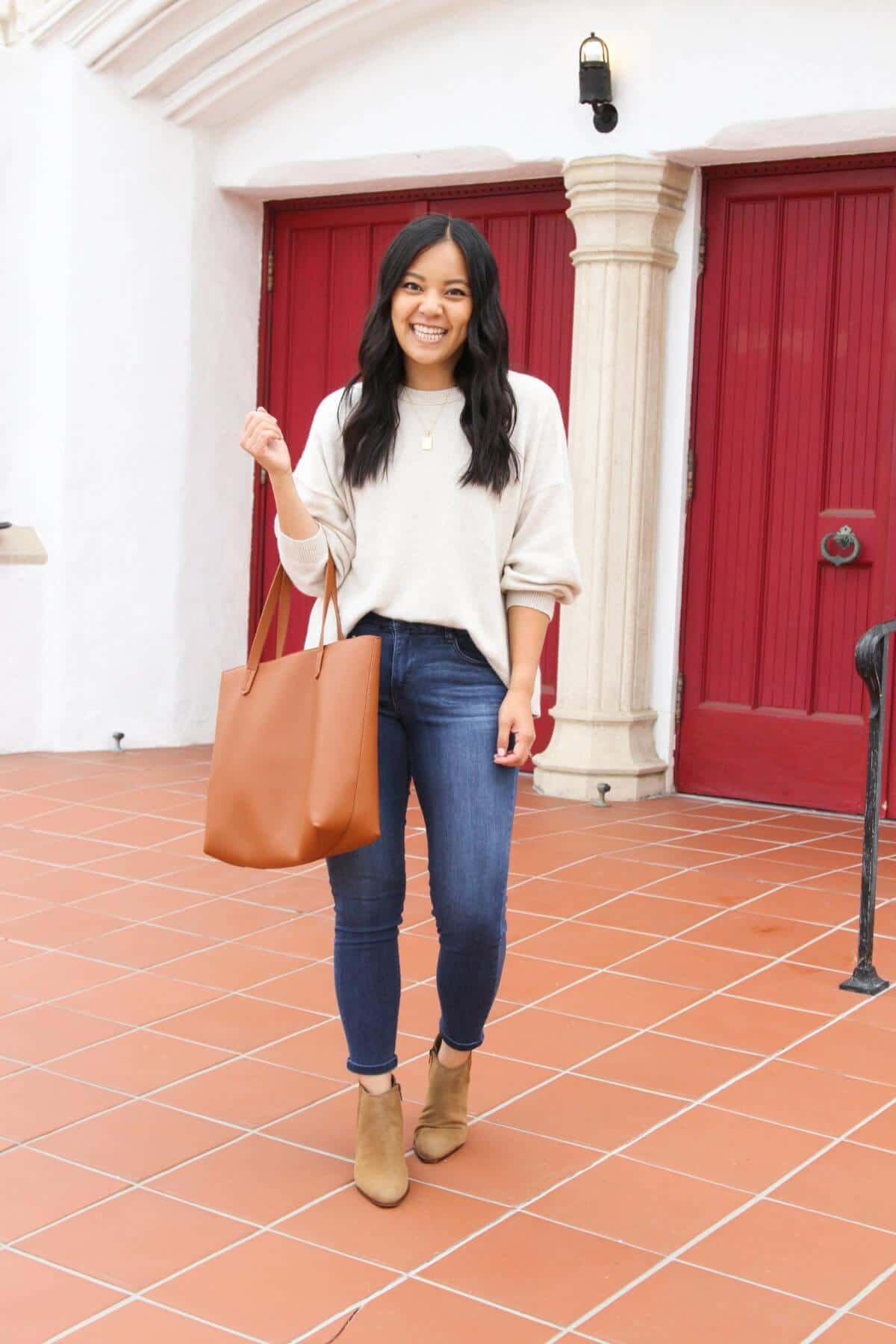 Nicer Casual Outfit: cream oversized sweater + medium blue ankle skinny jeans + gold initial pendant necklace + tan suede booties + tan tote