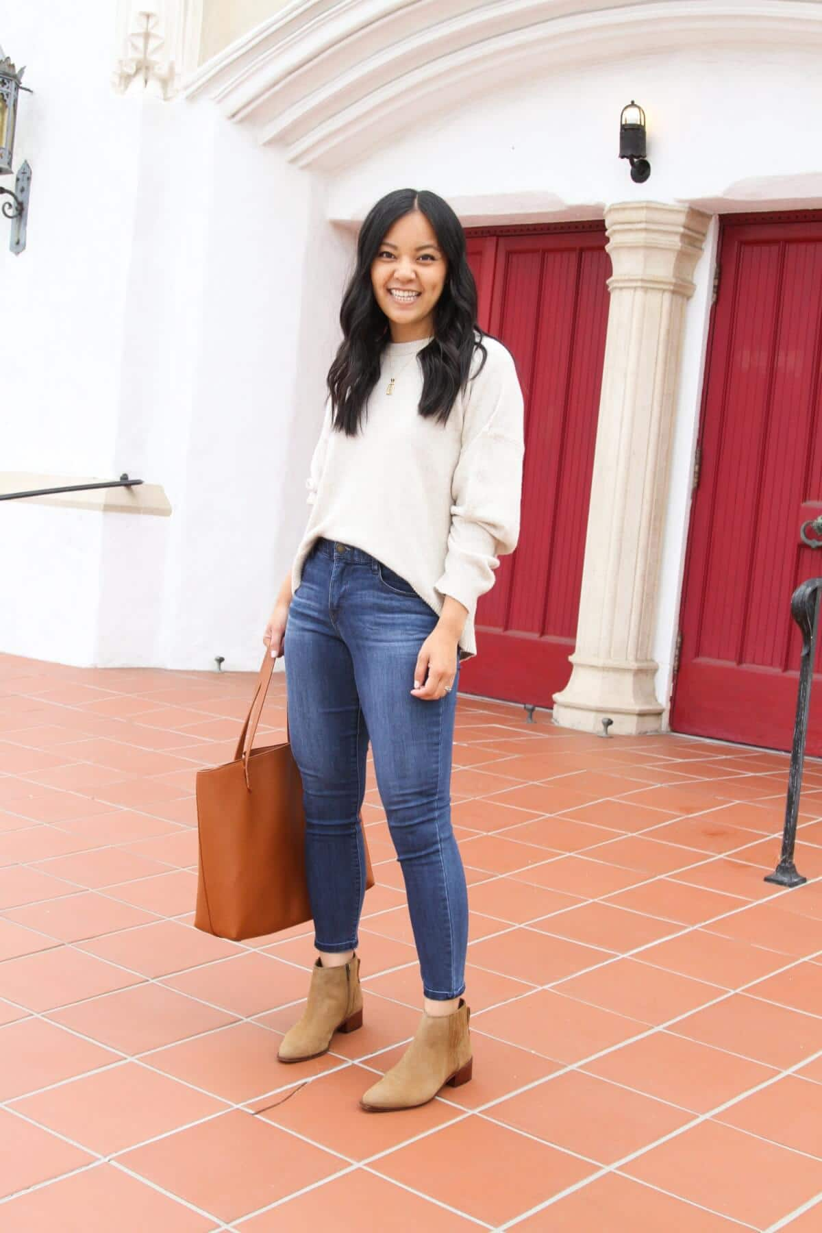 Nicer Casual Outfit: cream oversized sweater + medium blue ankle skinny jeans + gold initial pendant necklace + tan suede booties + tan tote side