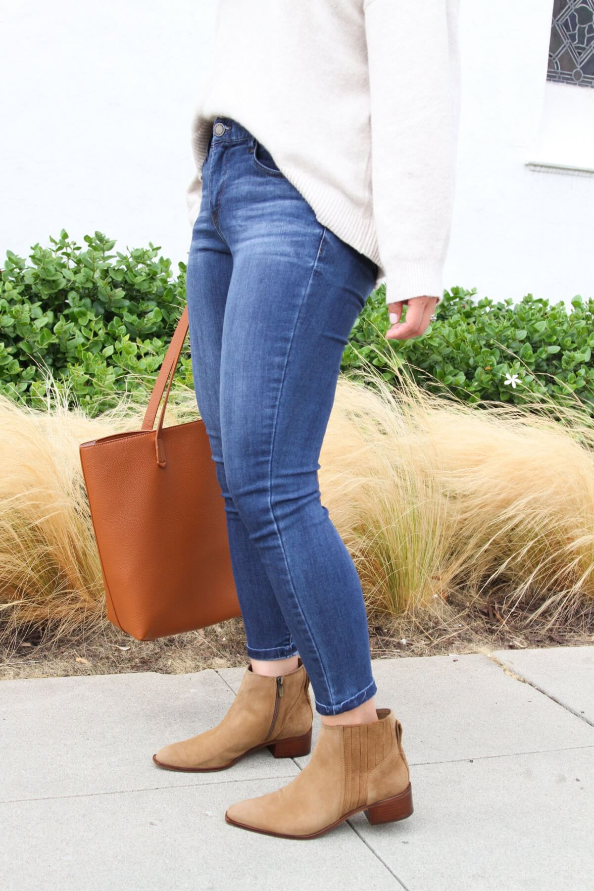 Nicer Casual Outfit: cream oversized sweater + medium blue ankle skinny jeans + tan suede booties + tan tote side