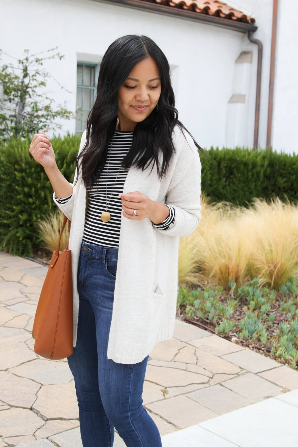 Nicer Casual Outfit: black and white striped long sleeve tee + medium blue jeans + cream long cardigan + gold pendant necklace + tan earrings + tan tote