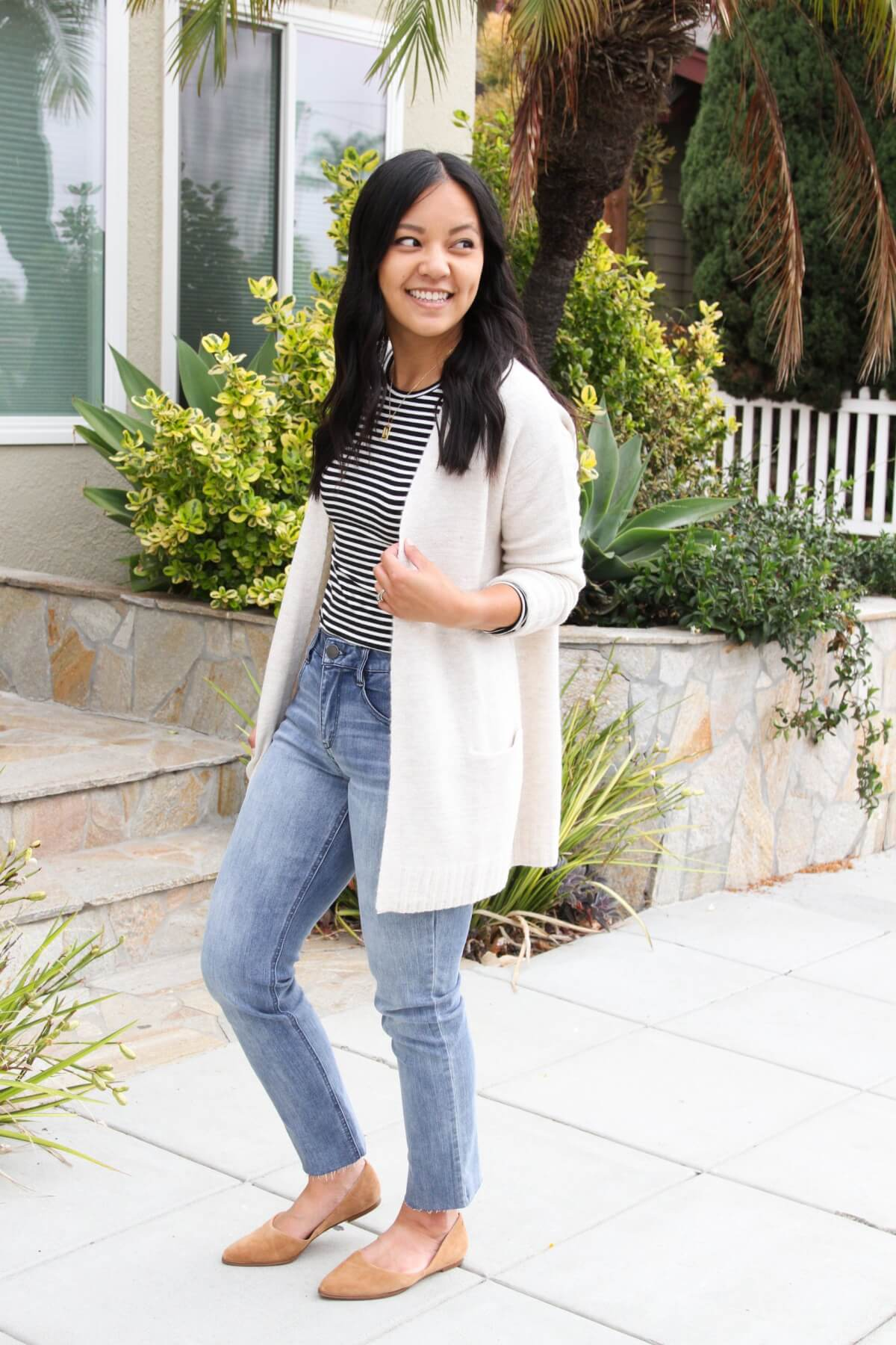 Nicer Casual Outfit: black and white striped long sleeve tee + light blue straight leg raw hem jeans + cream long cardigan + tan suede flats + gold initial pendant necklace side