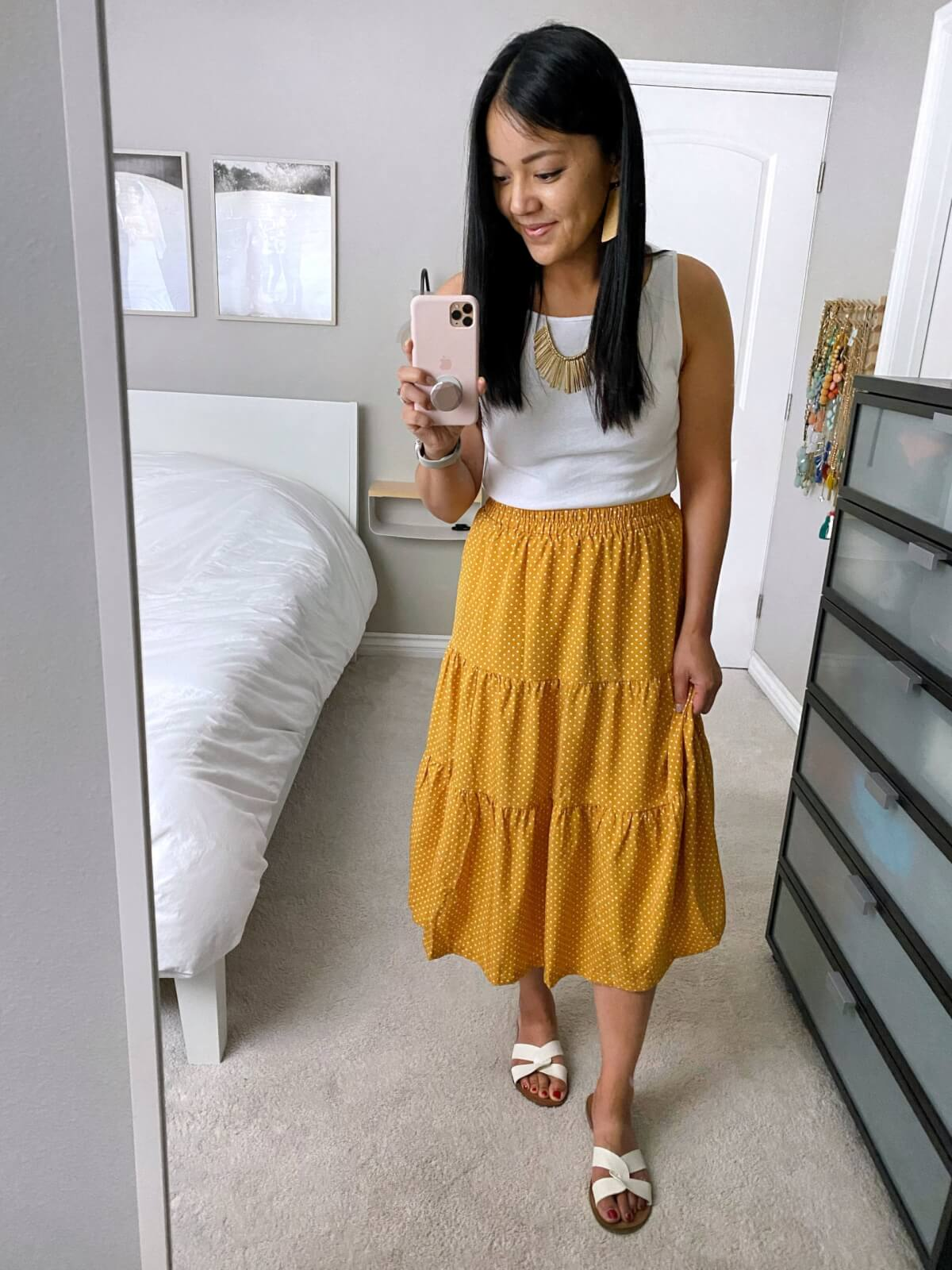 elevated casual summer outfit: white tank + yellow polka dot midi skirt + white slide sandals + gold earrings + gold bib necklace