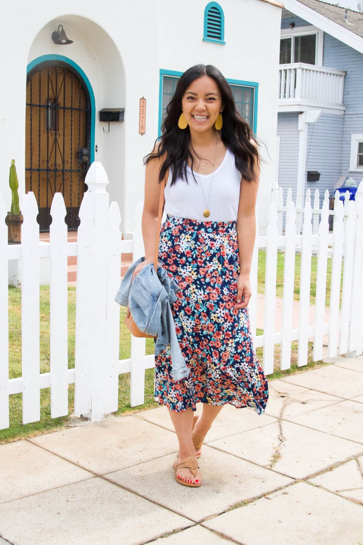 Elevated Casual Summer Outfit: white tank + floral midi skirt + yellow earrings + pendant necklace + leather braided thong sandals + denim jacket + tan crossbody bag