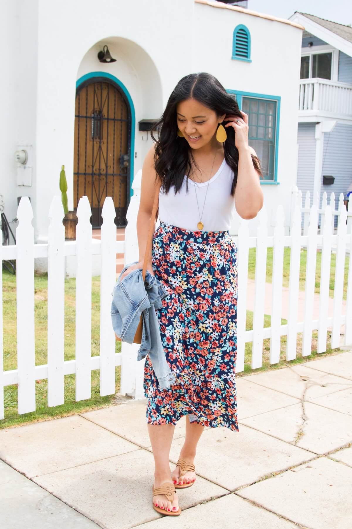Elevated Casual Summer Outfit: white tank + floral midi skirt + Nickel & Suede yellow earrings + pendant necklace + leather braided thong sandals + denim jacket + tan crossbody bag side