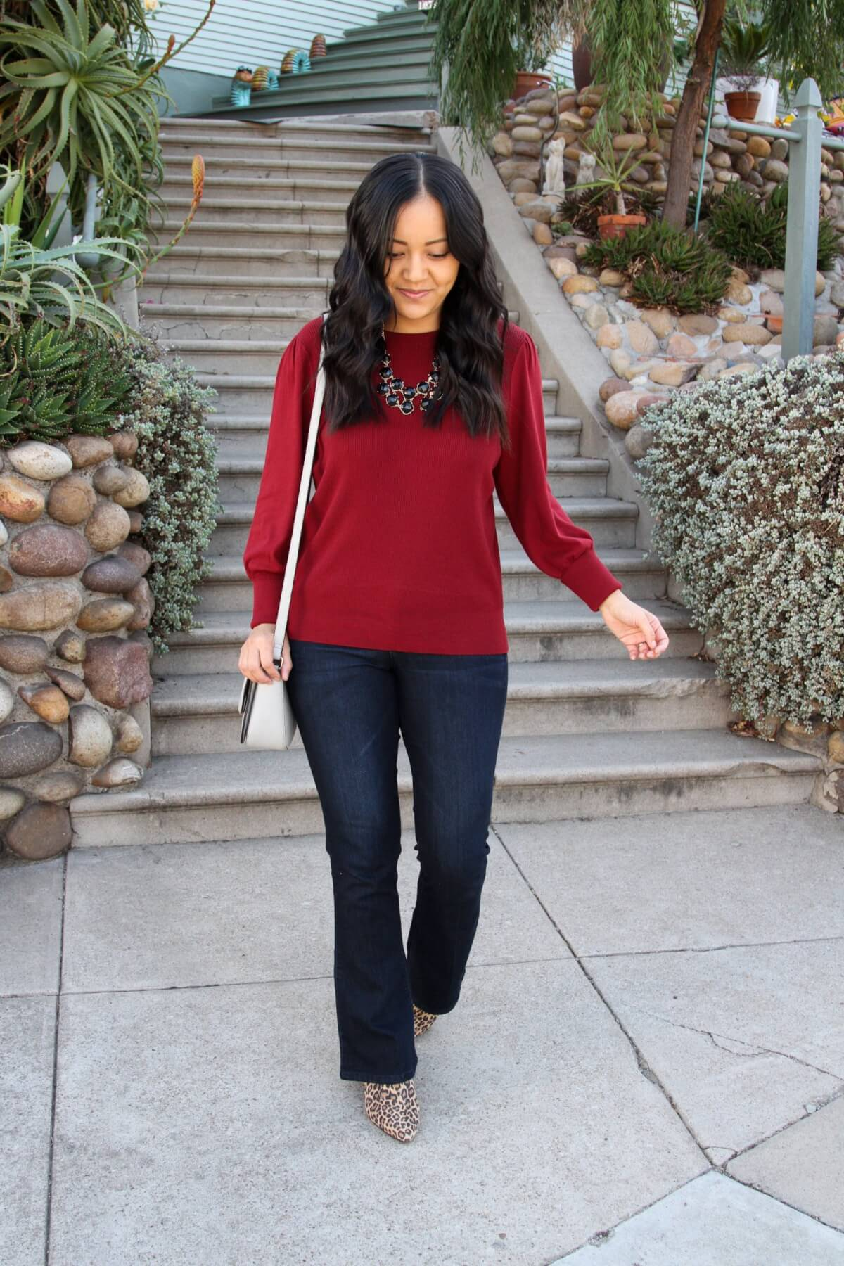 elevated casual outfit: red sweater + dark blue bootcut jeans + statement necklace + leopard booties + gray crossbody