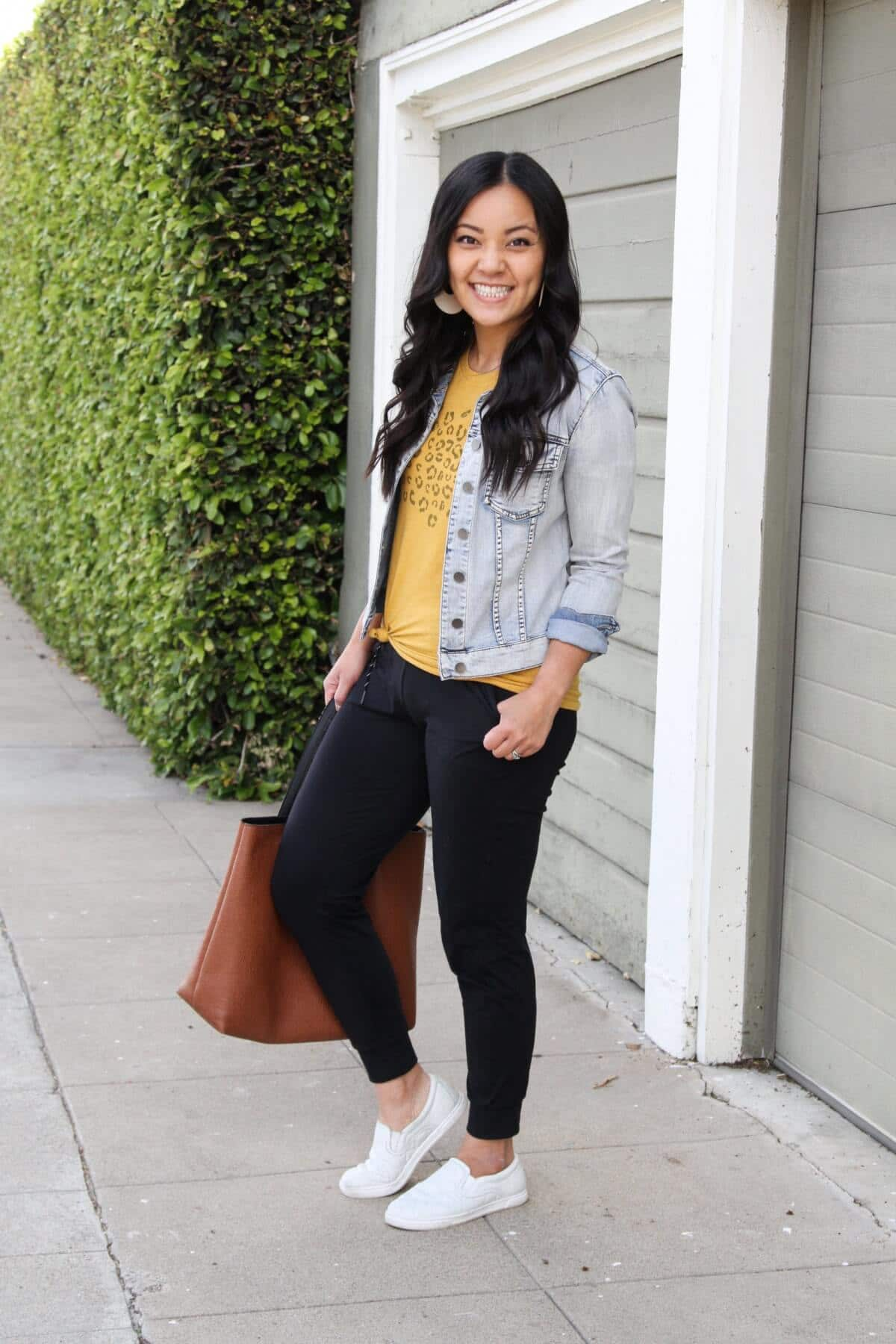 Casual Outfit Athleisure: yellow graphic tee + black joggers + denim jacket + white slip-on sneakers + tan tote