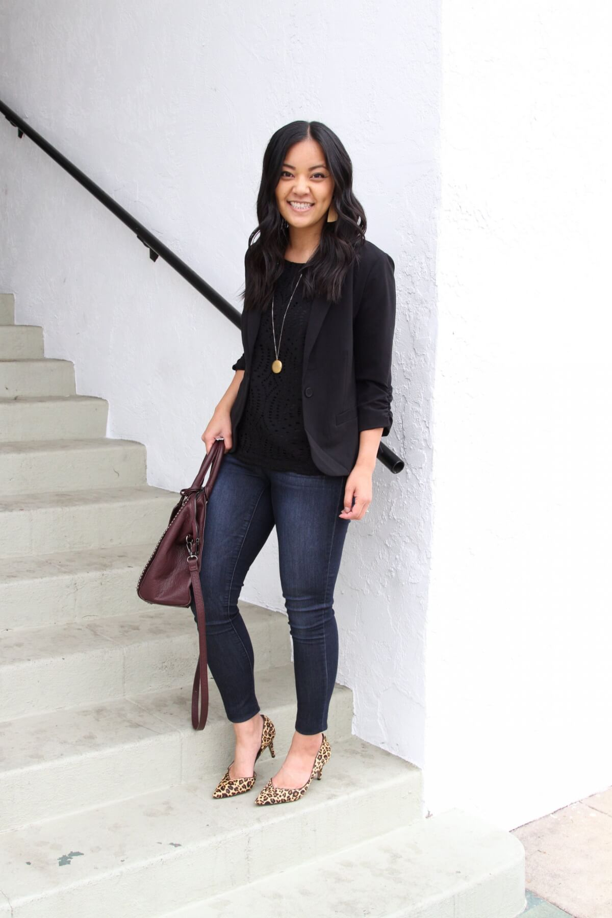 Elevated Casual Outfit: solid-colored top black + black blazer + blue jeans + leopard heels + gold pendant + burgundy bag