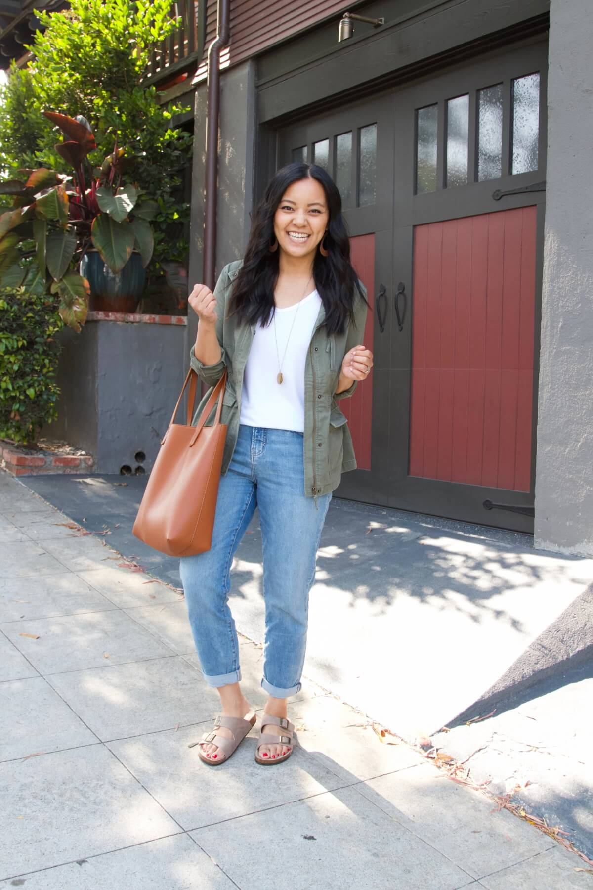 Summer to Fall Transition Casual Outfit: white t-shirt + olive utility jacket + light wash boyfriend jeans + taupe footbed sandals + tan earrings + gold pendant necklace + tan tote