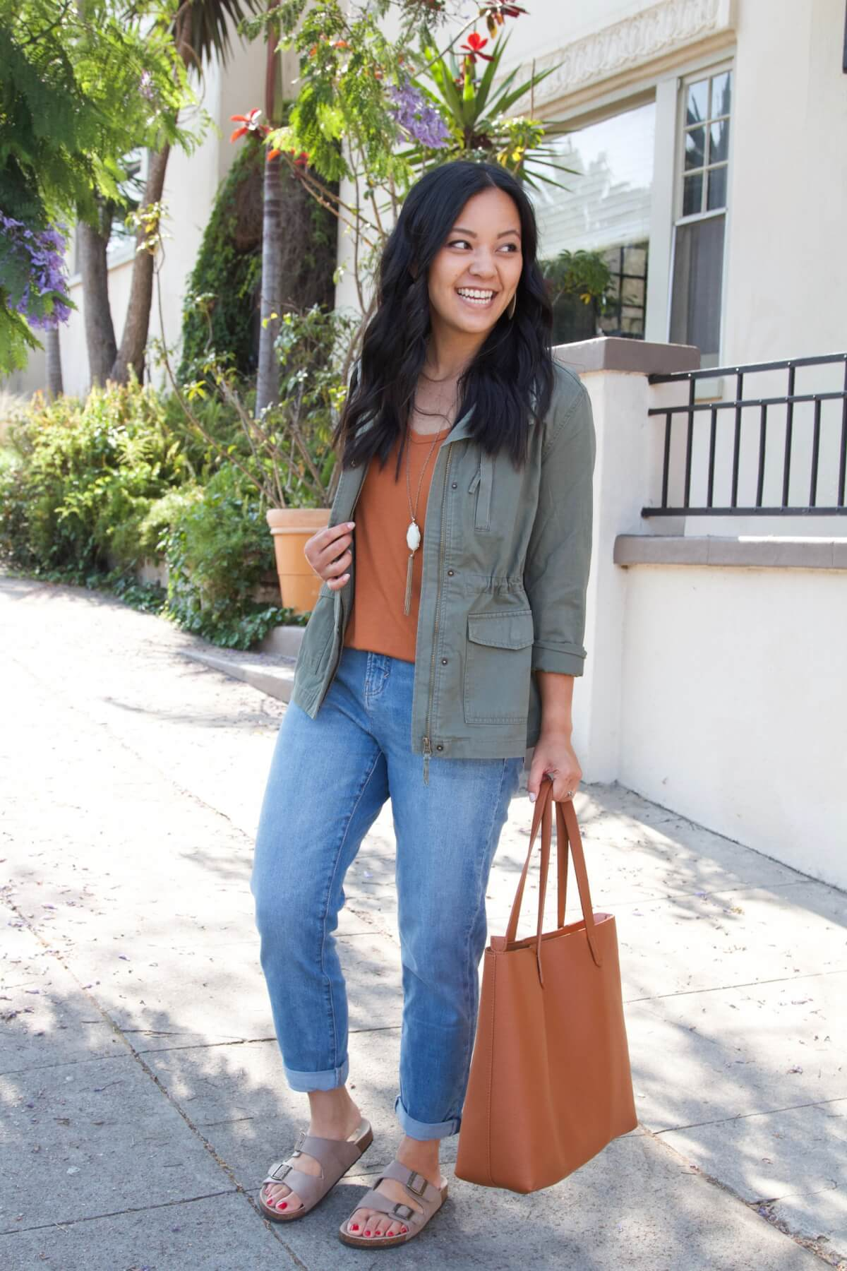 Casual Fall Outfit Summer to Early Fall Transition: olive utility jacket + pumpkin orange top + light straight leg jeans + taupe birkenstock sandals + pendant necklace + tan tote