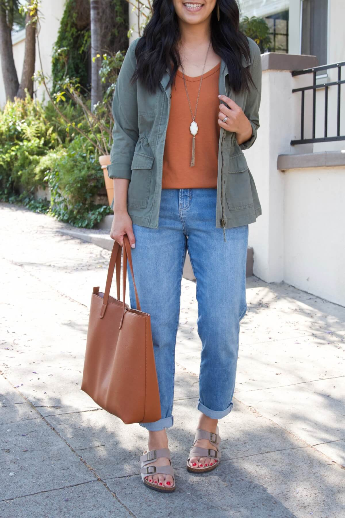 Casual Fall Outfit Summer to Early Fall Transition: olive utility jacket + pumpkin orange top + light denim + taupe birkenstock footbed sandals + pendant necklace + tan tote