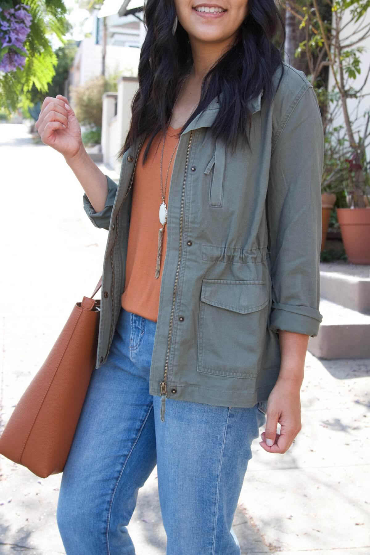 Casual Fall Outfit Summer to Early Fall Transition: olive utility jacket + pumpkin orange top + light denim + pendant necklace + tan tote close up