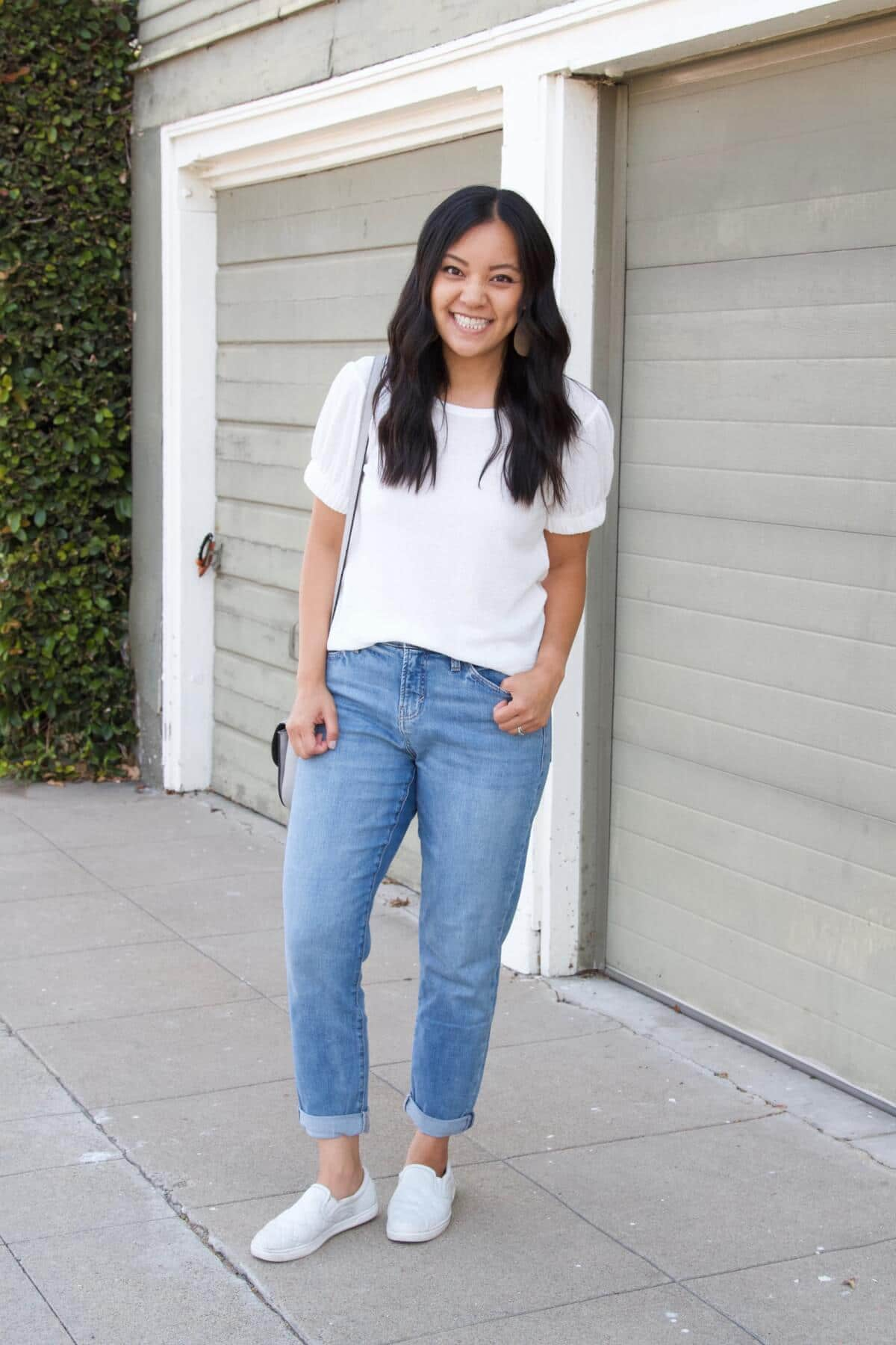 nicer casual outfit Summer to Early Fall Transition: white puff sleeve short sleeve top + light blue straight leg jeans + white slip-on sneakers + white earrings + gray crossbody purse