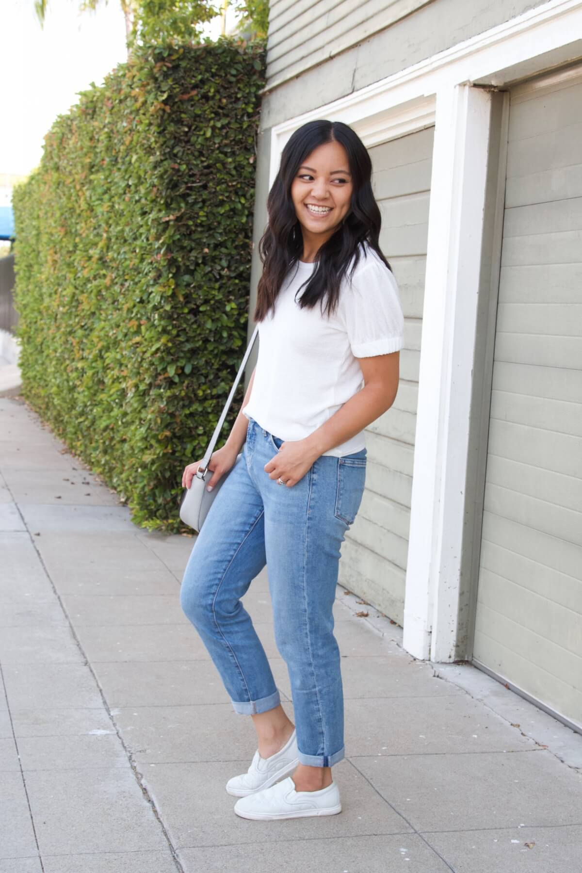 nicer casual outfit Summer to Early Fall Transition: white puff sleeve short sleeve top + light denim + white slip-on sneakers + gray crossbody purse side