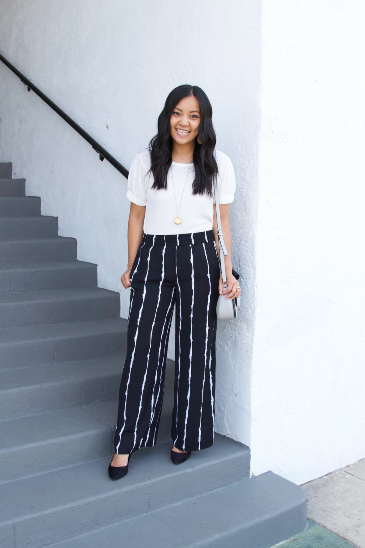 Elevated Nicer Casual Outfit Summer to Early Fall Transition: white puff sleeve top + black and white striped wide leg pants + black heels + white earrings + gold pendant necklace + gray crossbody purse