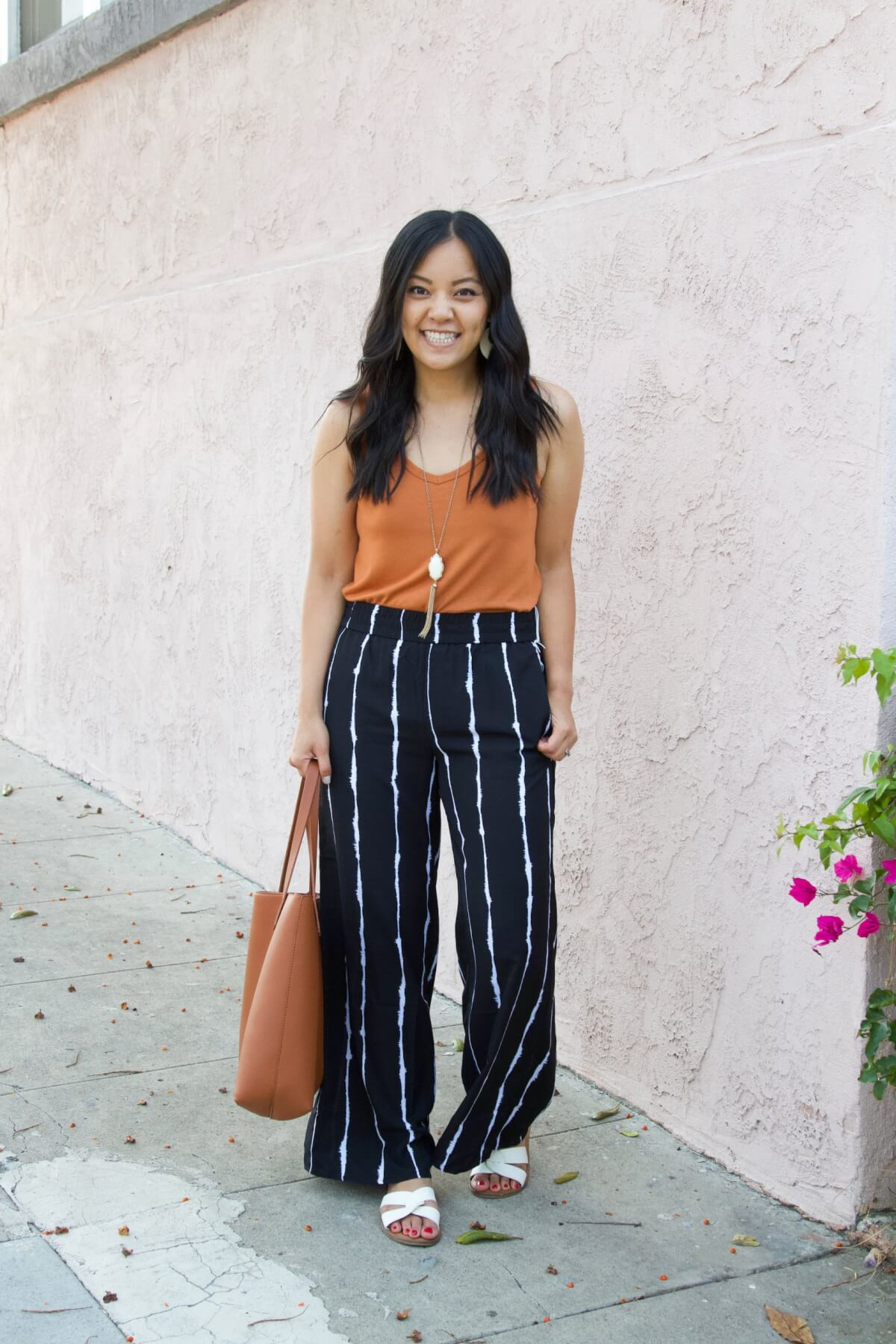 Nicer Casual Outfit for Summer to Early Fall Transition: pumpkin orange tank + black and white striped wide leg pants + white slide sandals + white earrings + pendant necklace + tan tote