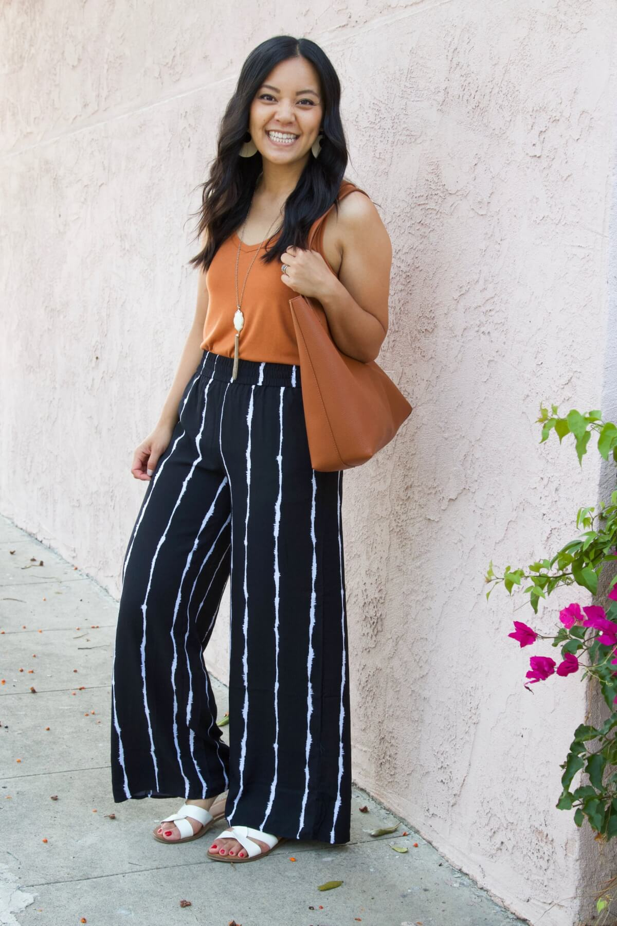 Nicer Casual Outfit for Summer to Early Fall Transition: copper orange tank + black and white striped wide leg pants + white slide sandals + white earrings + pendant necklace + tan tote side view