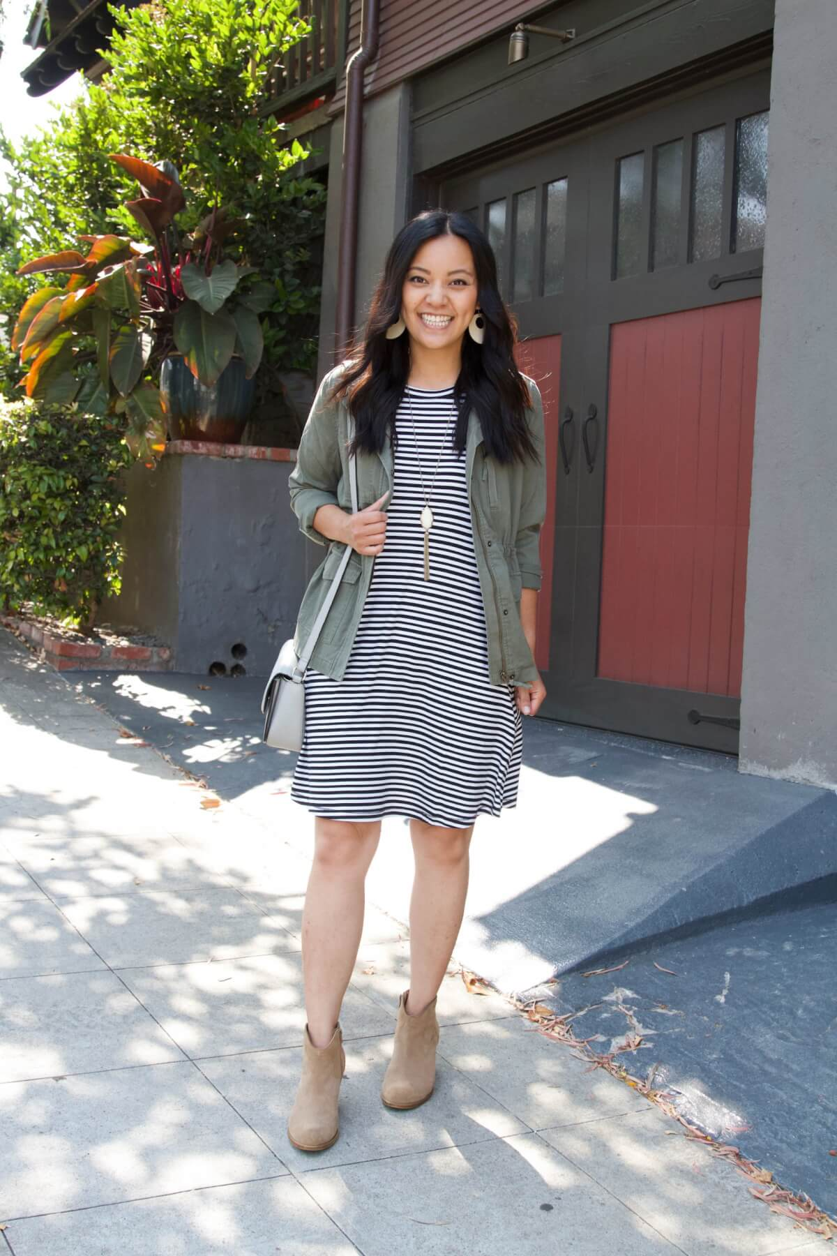 Nicer Casual Outfit for Summer to Early Fall Transition: black and white striped dress + olive utility jacket + taupe suede booties + white earrings + pendant necklace + gray crossbody purse