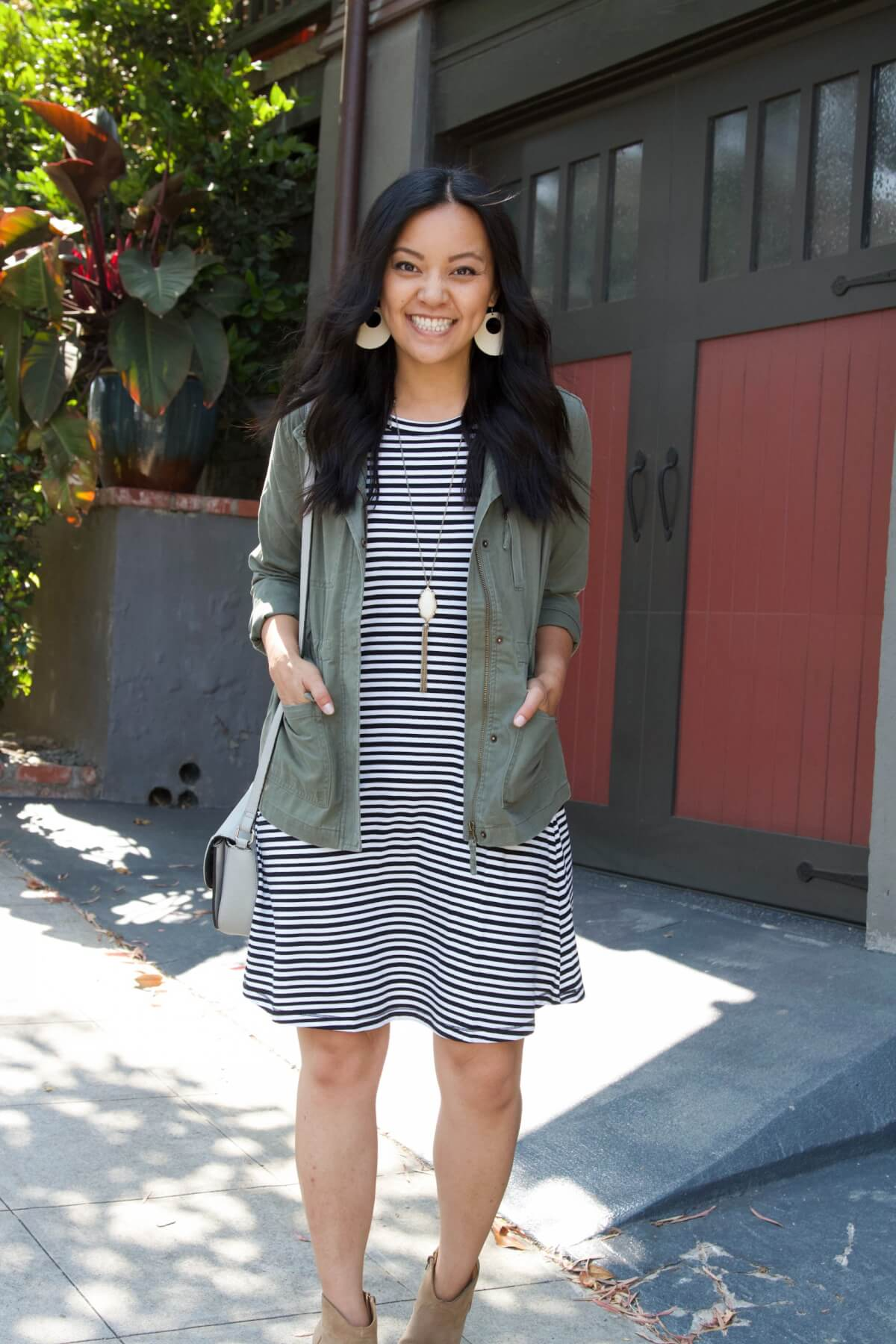 Nicer Casual Outfit for Summer to Early Fall Transition: black and white striped t-shirt dress + olive utility jacket + taupe suede booties + white earrings + tassel pendant necklace + gray crossbody purse