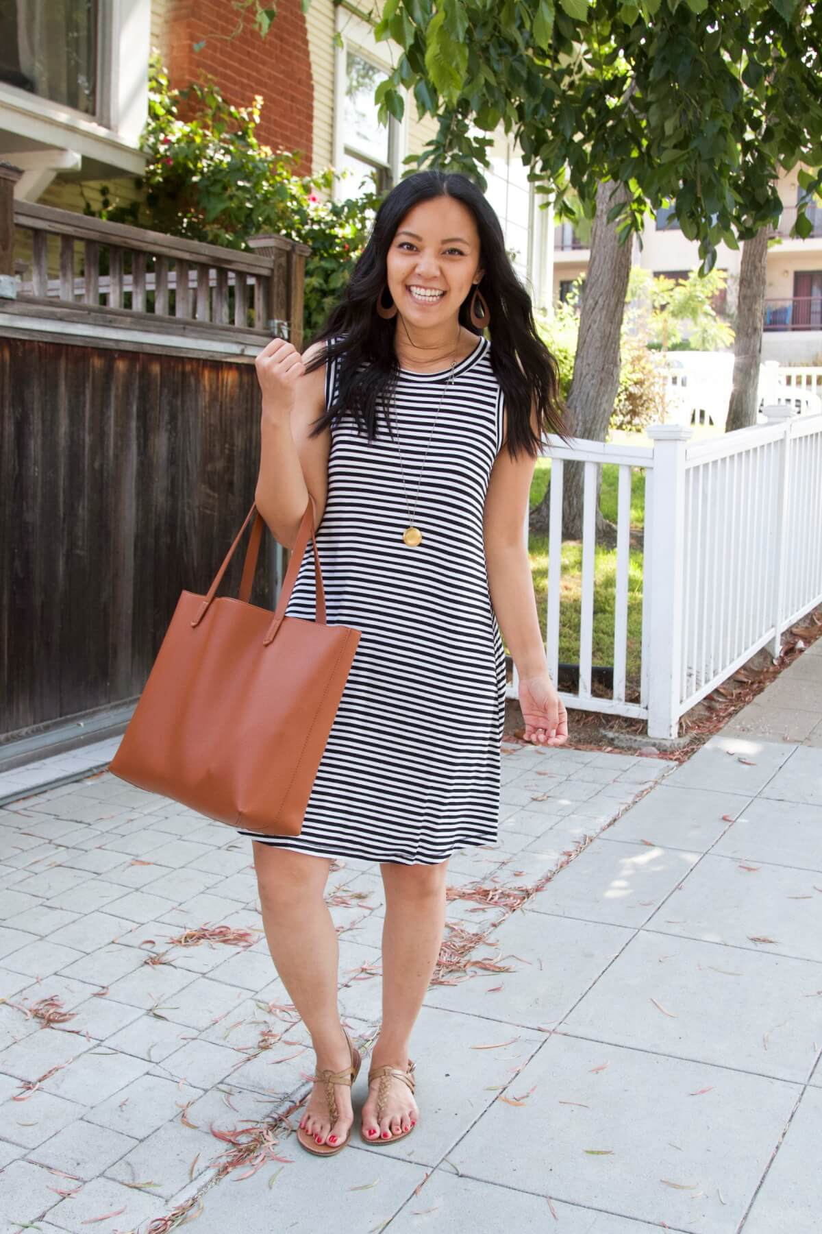 Nicer Casual Outfit for Summer to Early Fall Transition: black and white striped t-shirt dress + tan t-strap sandals + tan earrings + gold pendant necklace + tan tote
